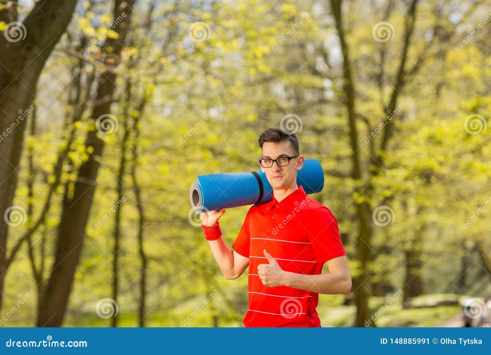 Homem novo dos esportes no t-shirt vermelho que levanta em um parque da mola com uma esteira azul da ioga Sua classe das mostras