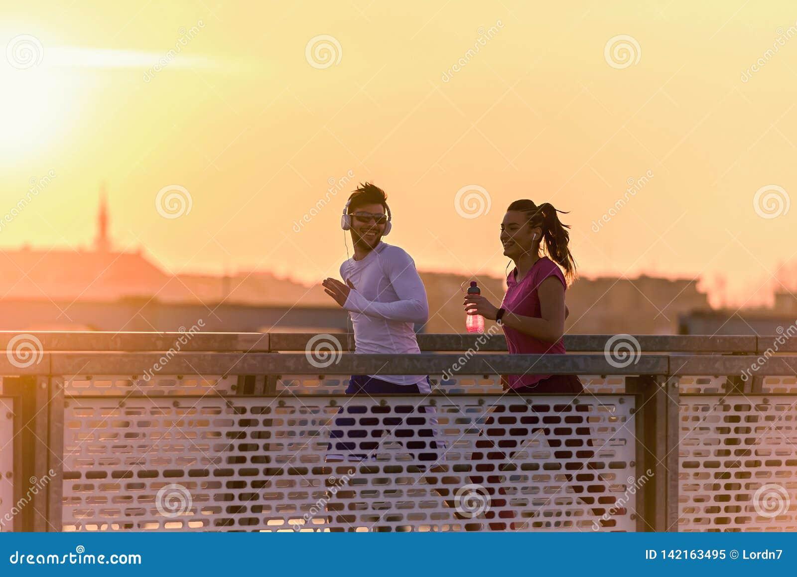 Homem novo e mulher que movimentam-se junto sobre a ponte no por do sol ou no nascer do sol