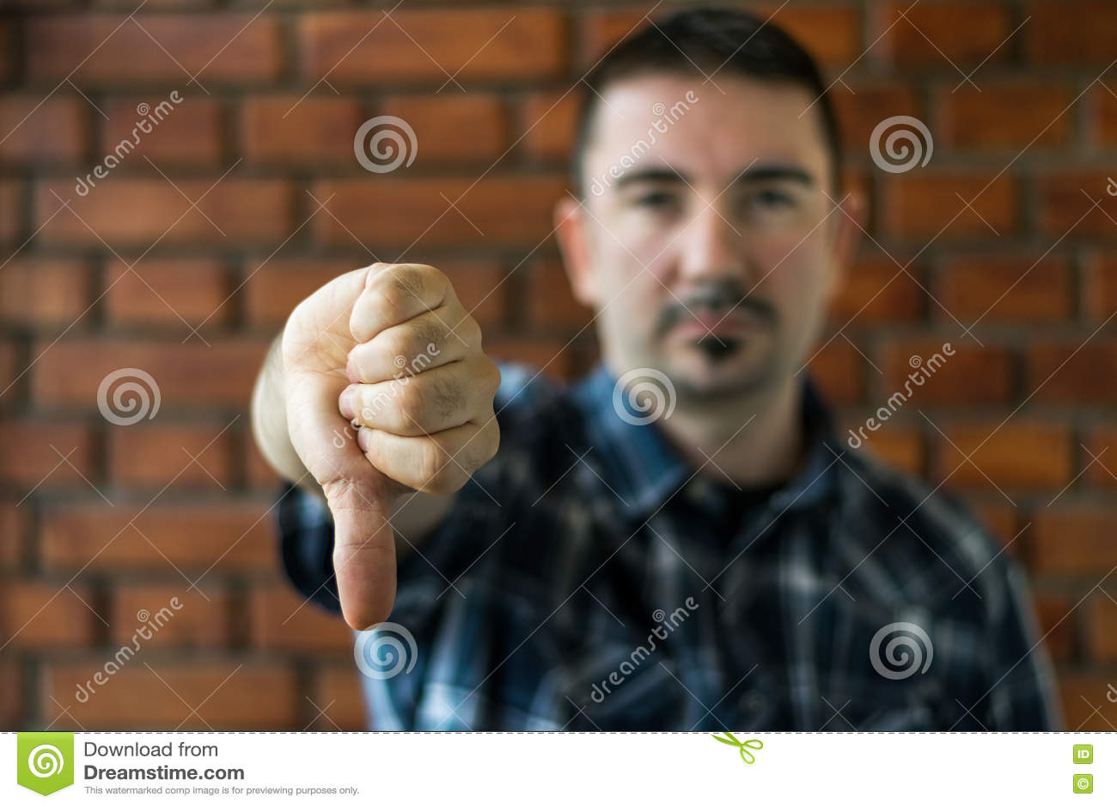 Homem novo em seu 30s que mostra os polegares para baixo Foco seletivo