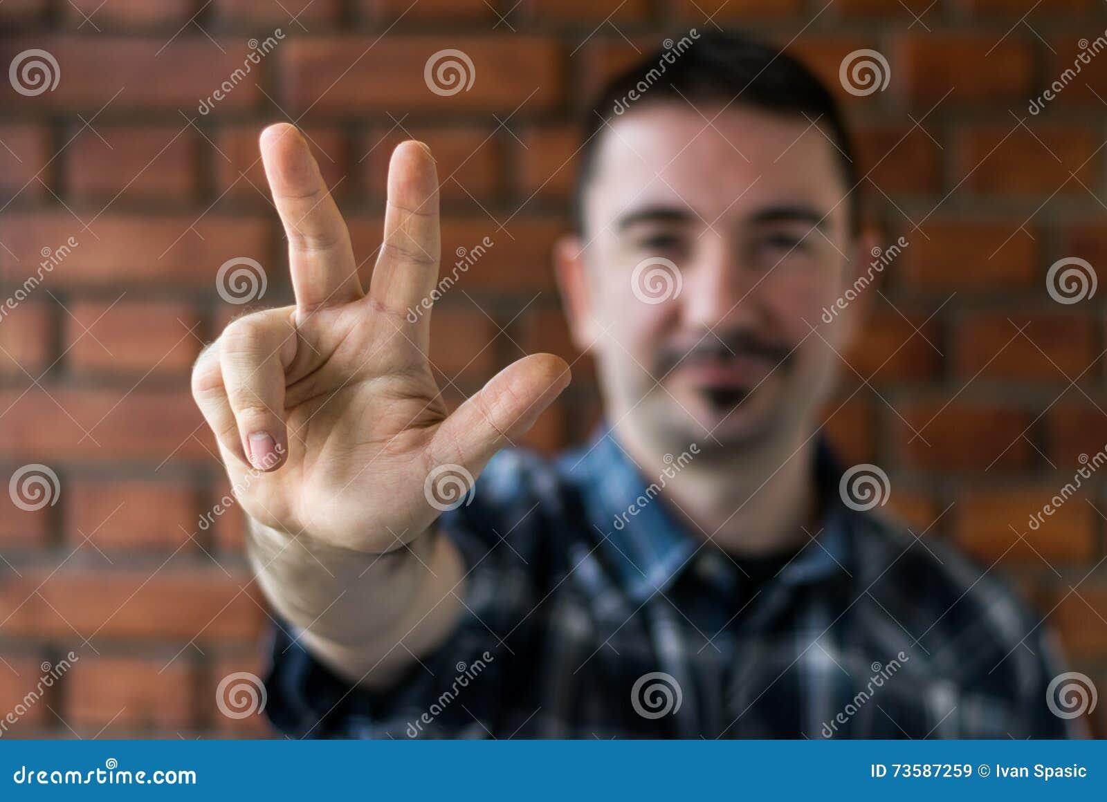 Homem novo em seu 30s que mostra três dedos Foco seletivo