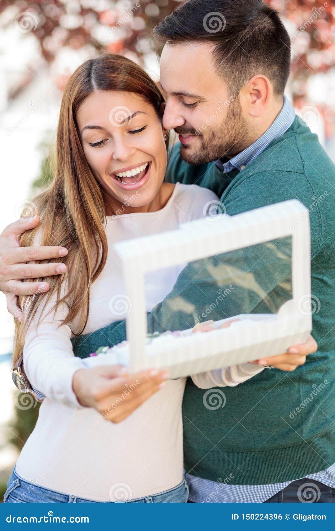 Homem novo feliz que abraça sua esposa ou amiga A mulher está sorrindo após ter aberto uma caixa de presente