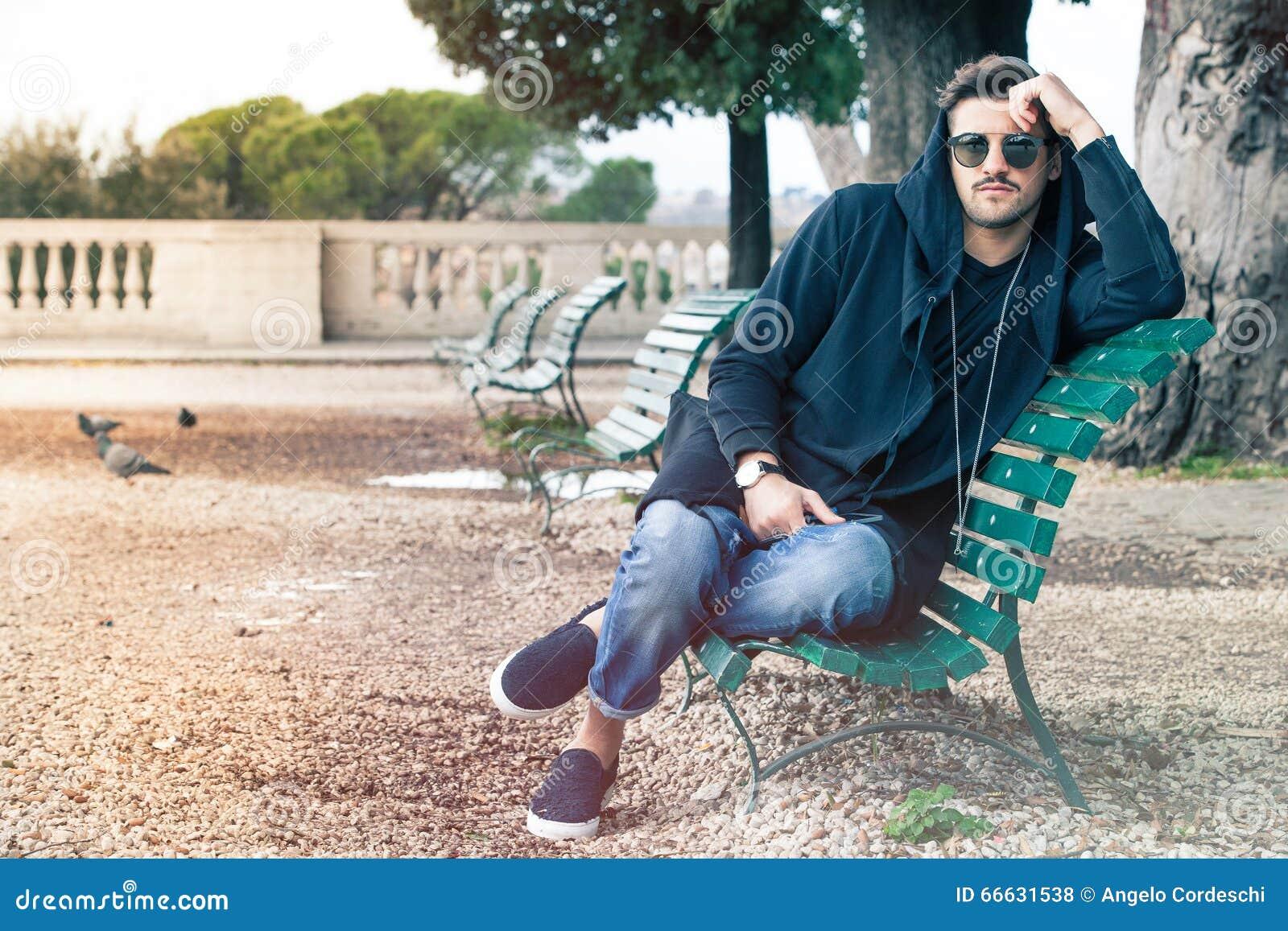 Homem novo fresco elegante com os óculos de sol que relaxam em um banco