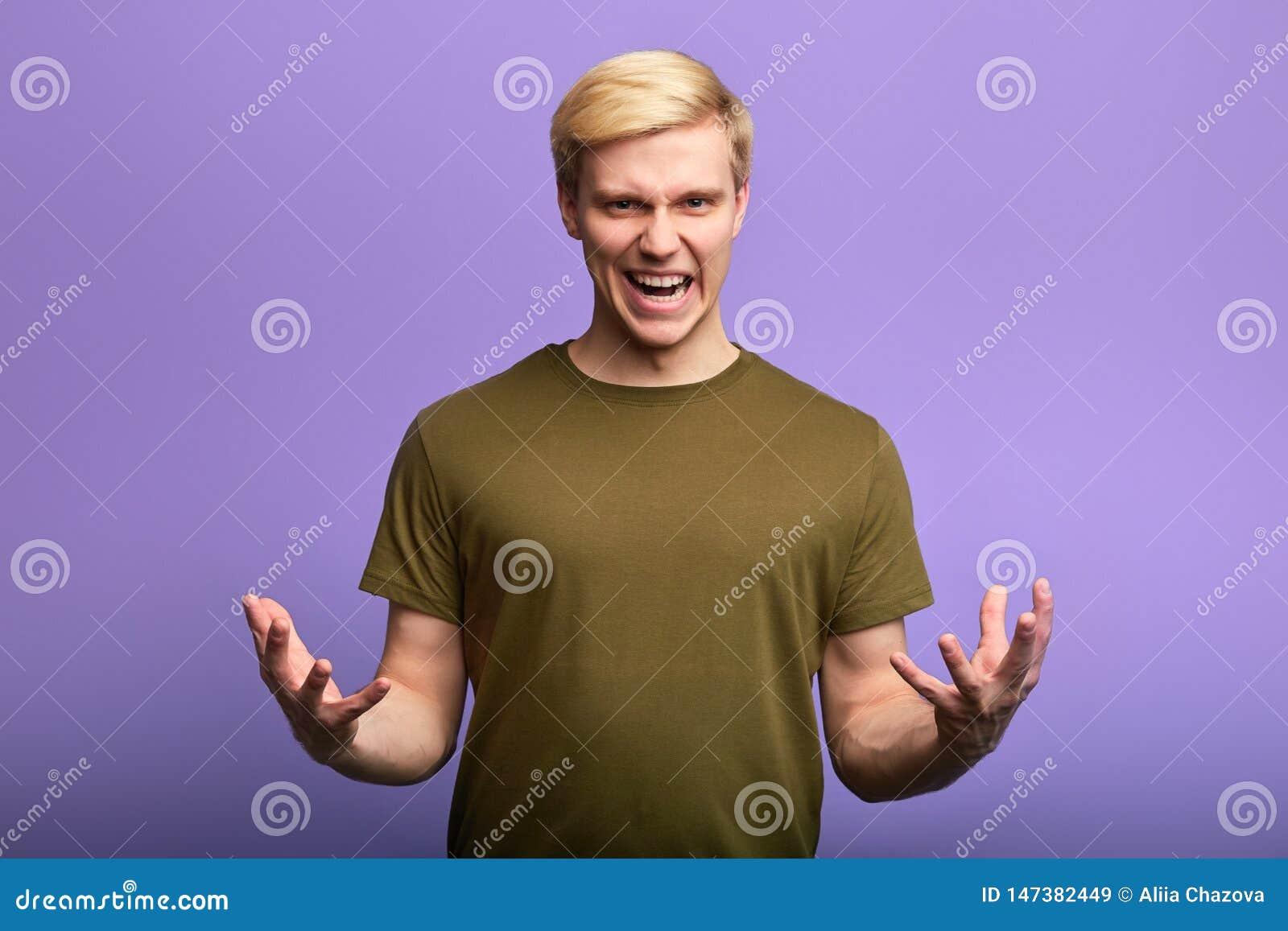 Homem novo frustrante infeliz irritado com braços para fora, gritaria em alguém