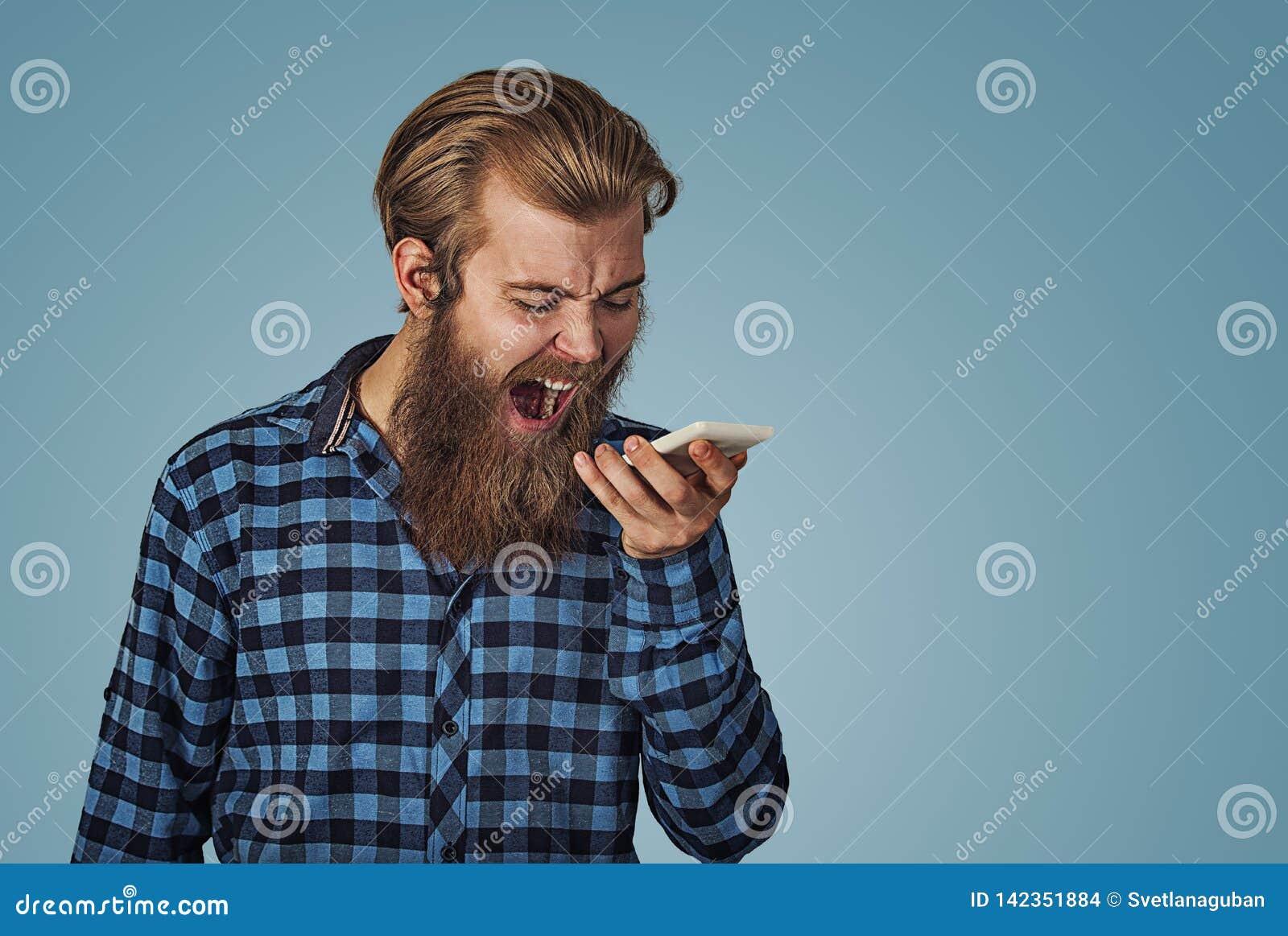 Homem novo irritado que grita no telefone celular