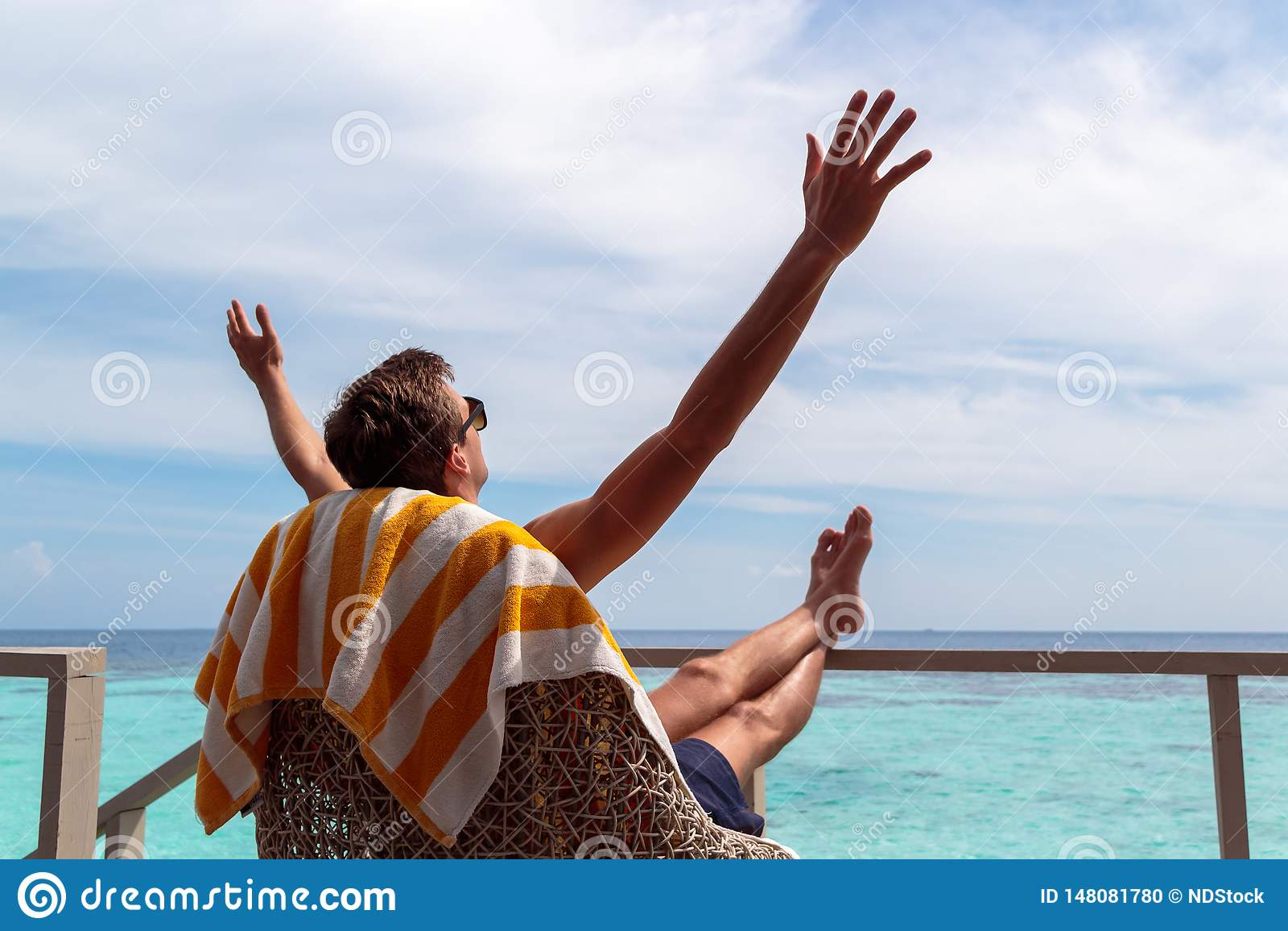 Homem novo no roupa de banho que relaxa em um terra?o e que aprecia a liberdade em um destino tropical Bra?os levantados