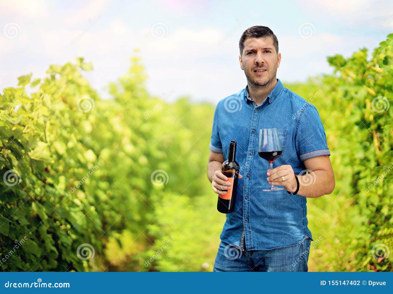 Homem novo no vinhedo com um vidro e uma garrafa do vinho tinto em suas mãos Homem que aprecia o tempo de colheita na exploração