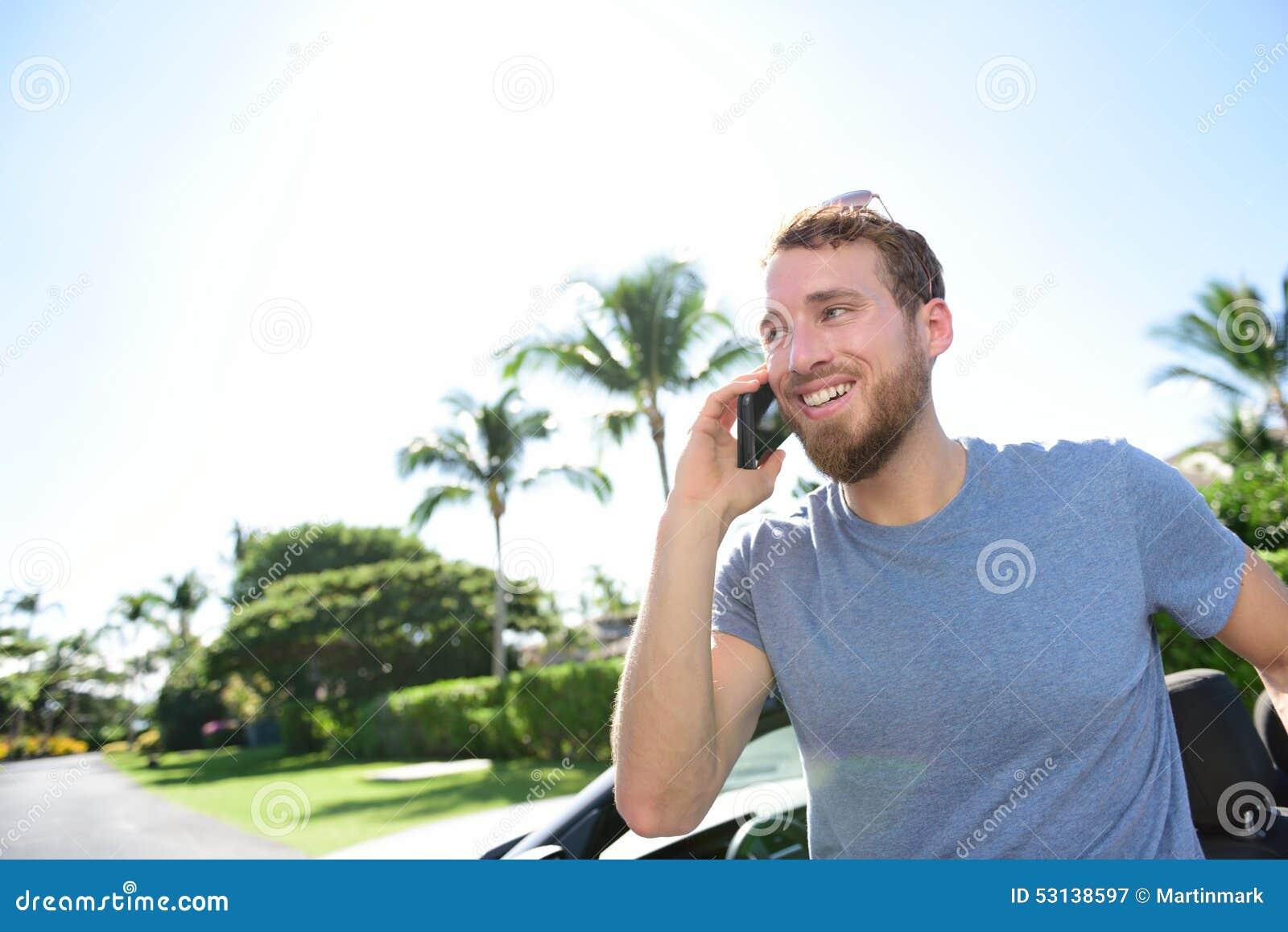 Homem novo ocasional esperto urbano que fala no smartphone