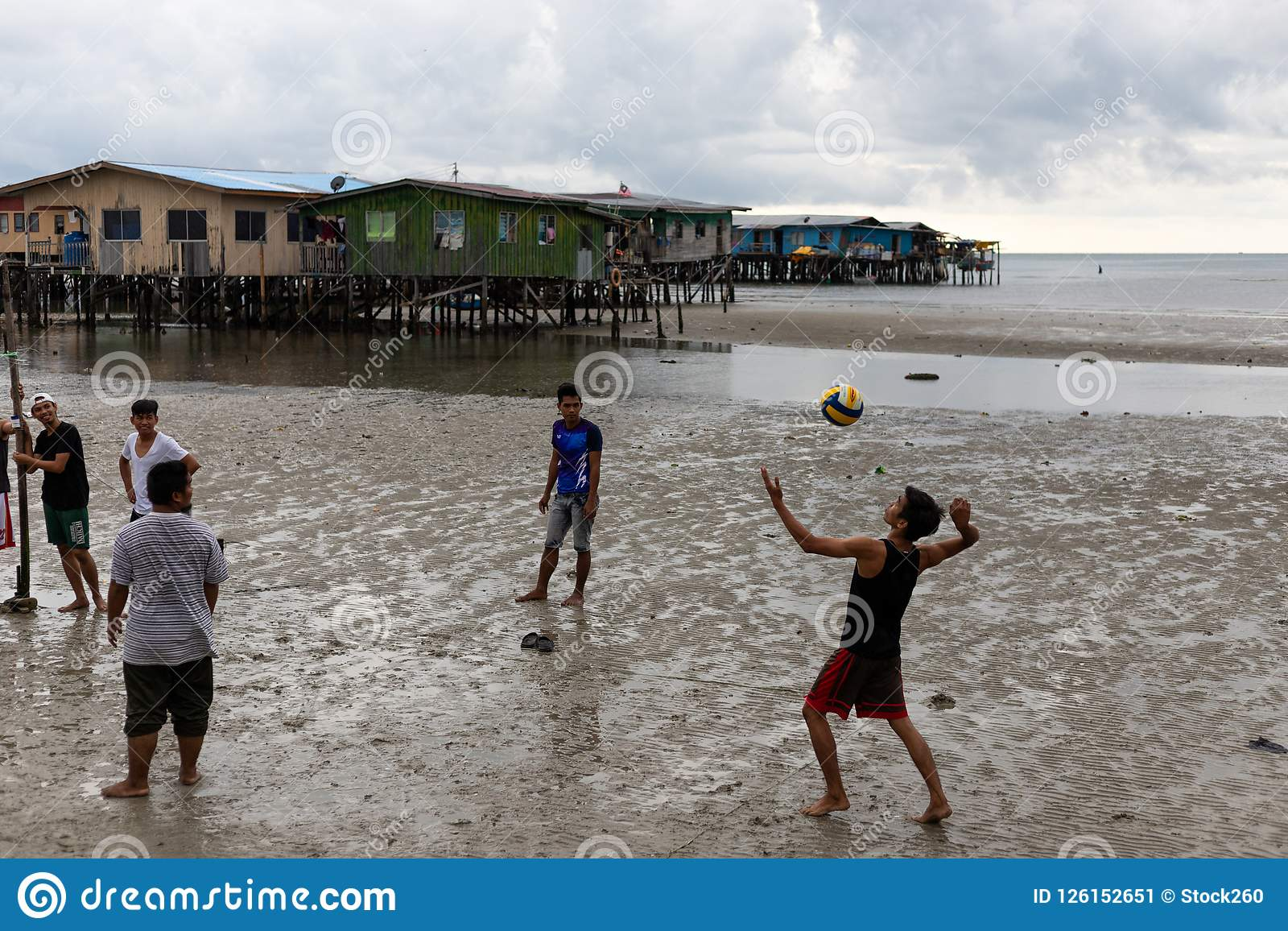 Homem novo pobre Povert da cidade asiática do lado de mar do voleibol do serviço do menino