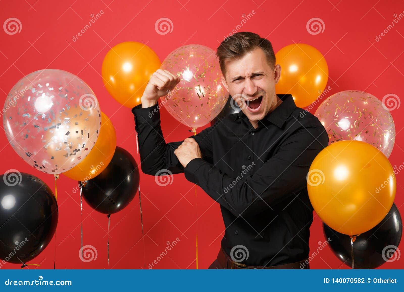 Homem novo poderoso na camisa clássica que mostra o bíceps, gritando em balões de ar vermelhos brilhantes do fundo ` S do Valenti