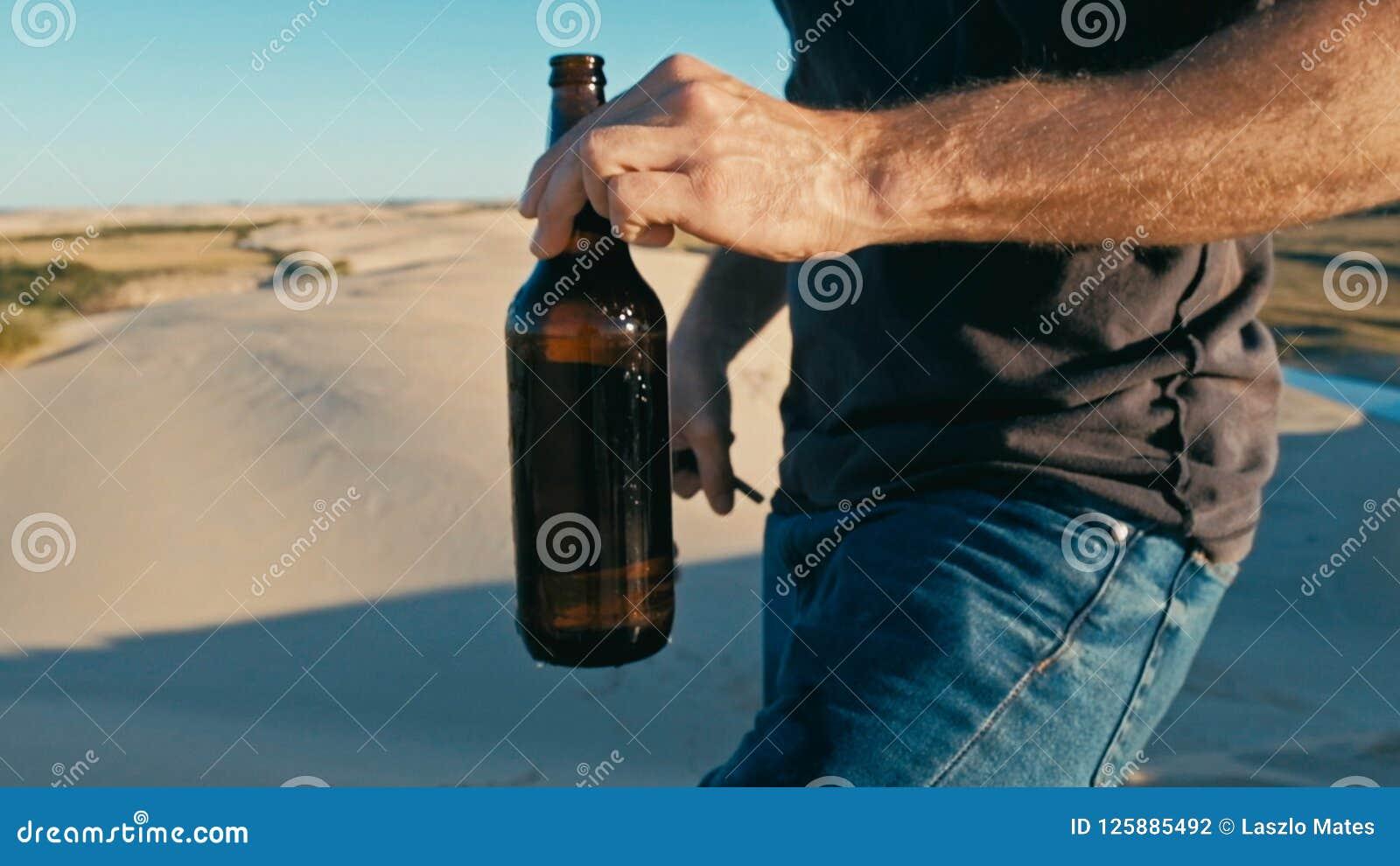 Homem novo que abre uma garrafa da cerveja exterior nas dunas de areia do deserto