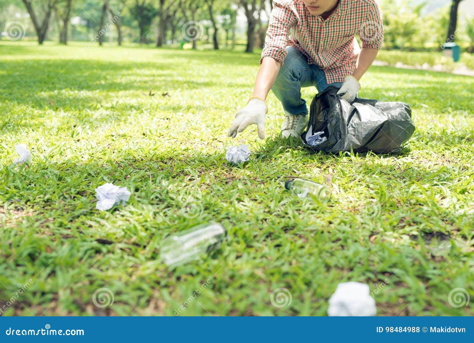 Homem novo que agacha-se para desperdiçar e que escolhe o acima no saco do escaninho