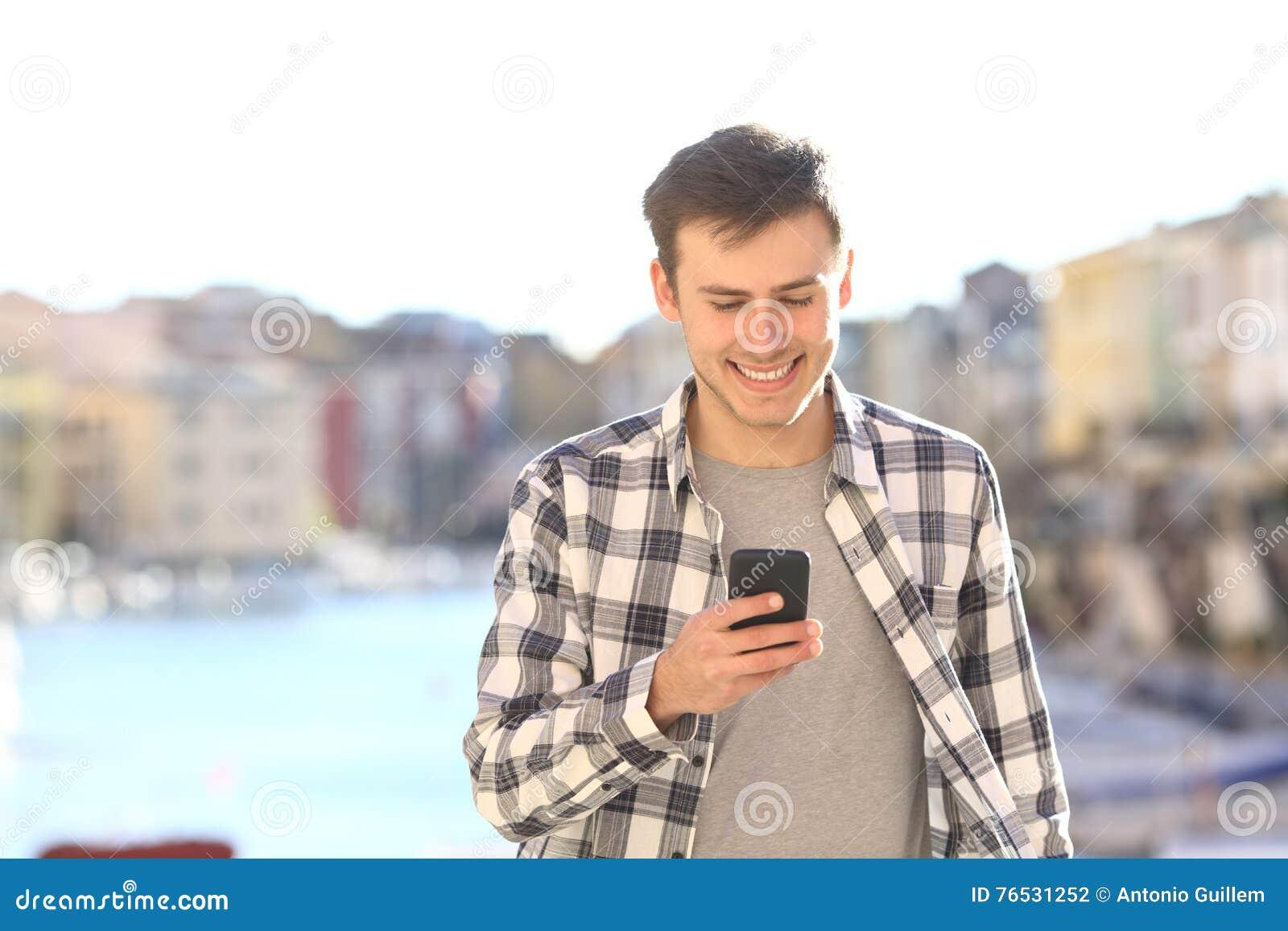 Homem novo que anda e que usa o telefone esperto