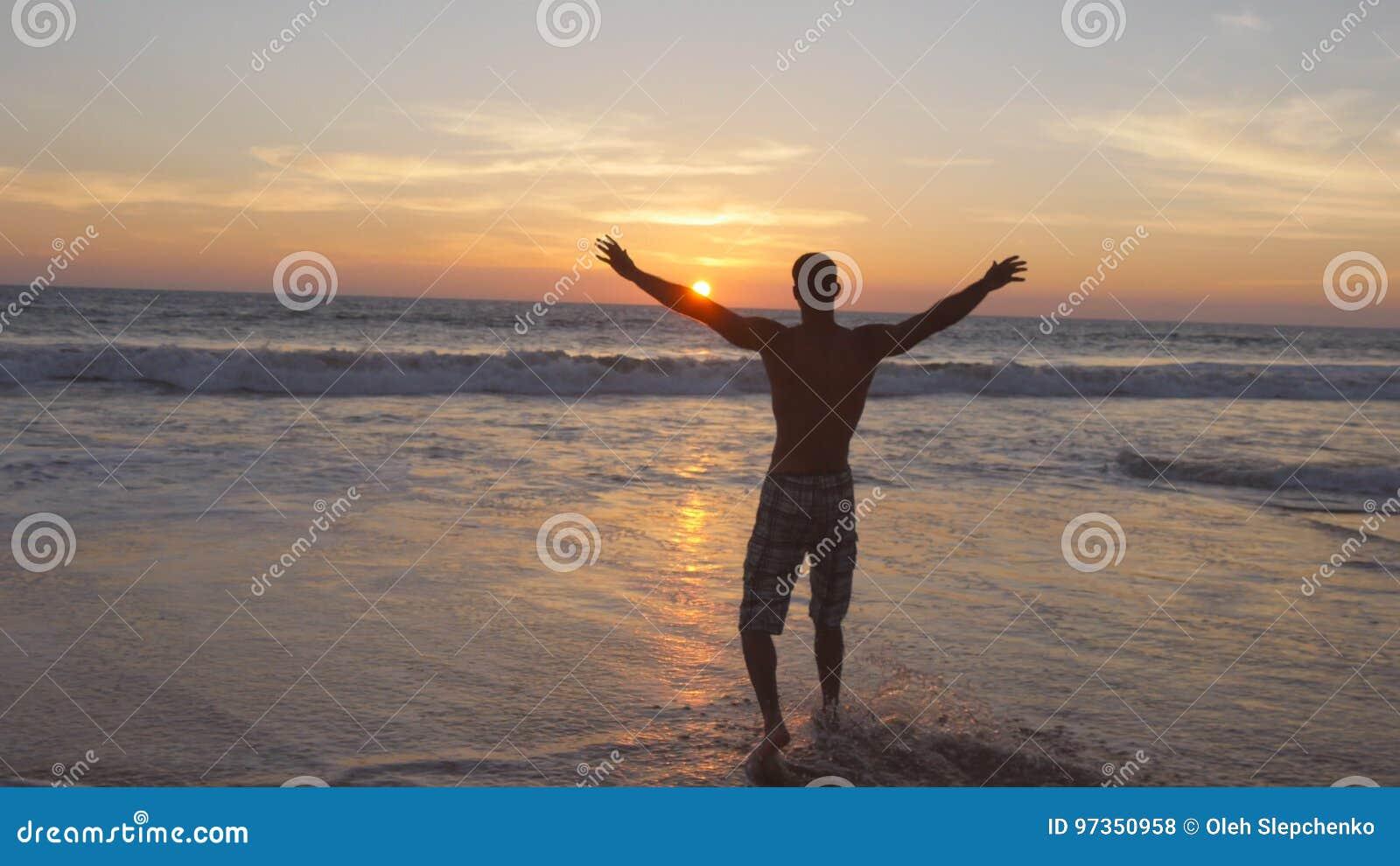 Homem novo que anda na água do oceano na praia no por do sol e nas mãos levantadas Indivíduo desportivo que está na costa de mar