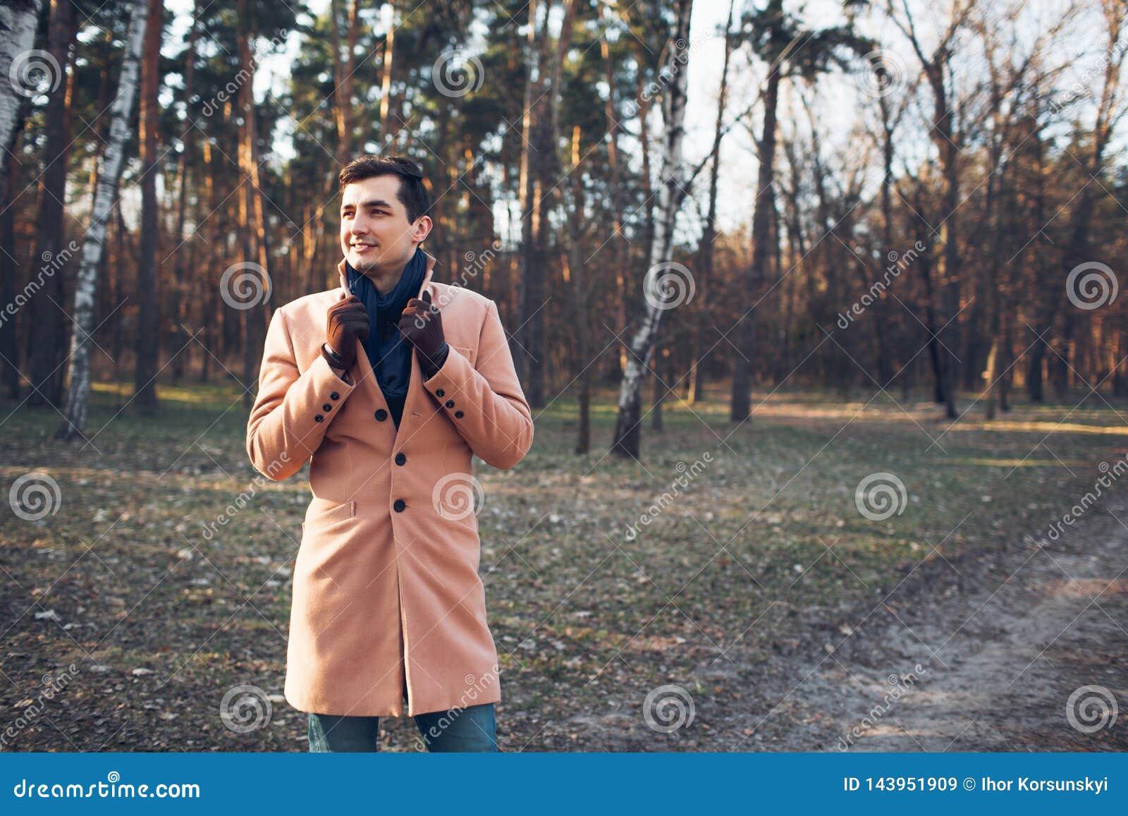 Homem novo que anda na floresta na natureza em um revestimento de creme