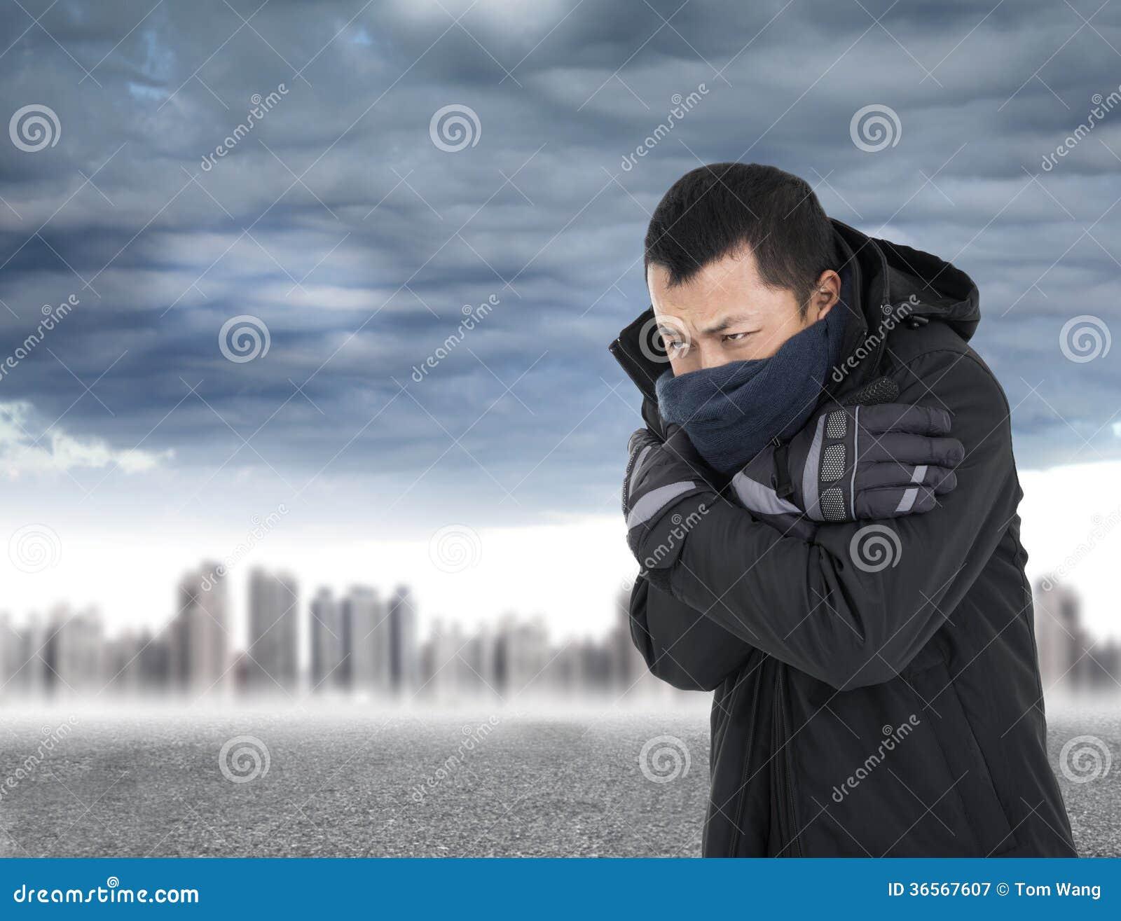Homem novo que aperta o corpo no tempo frio do ar livre