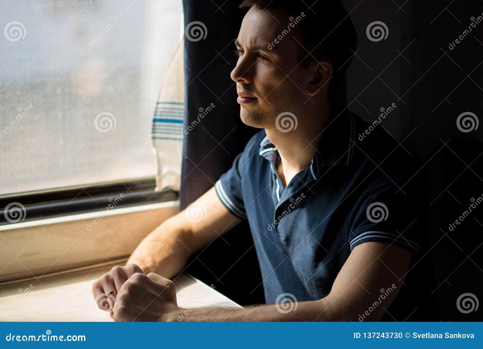 Homem novo que aprecia o curso do trem - deixando seu carro em casa, olha fora da janela, tem o tempo para admirar a paisagem
