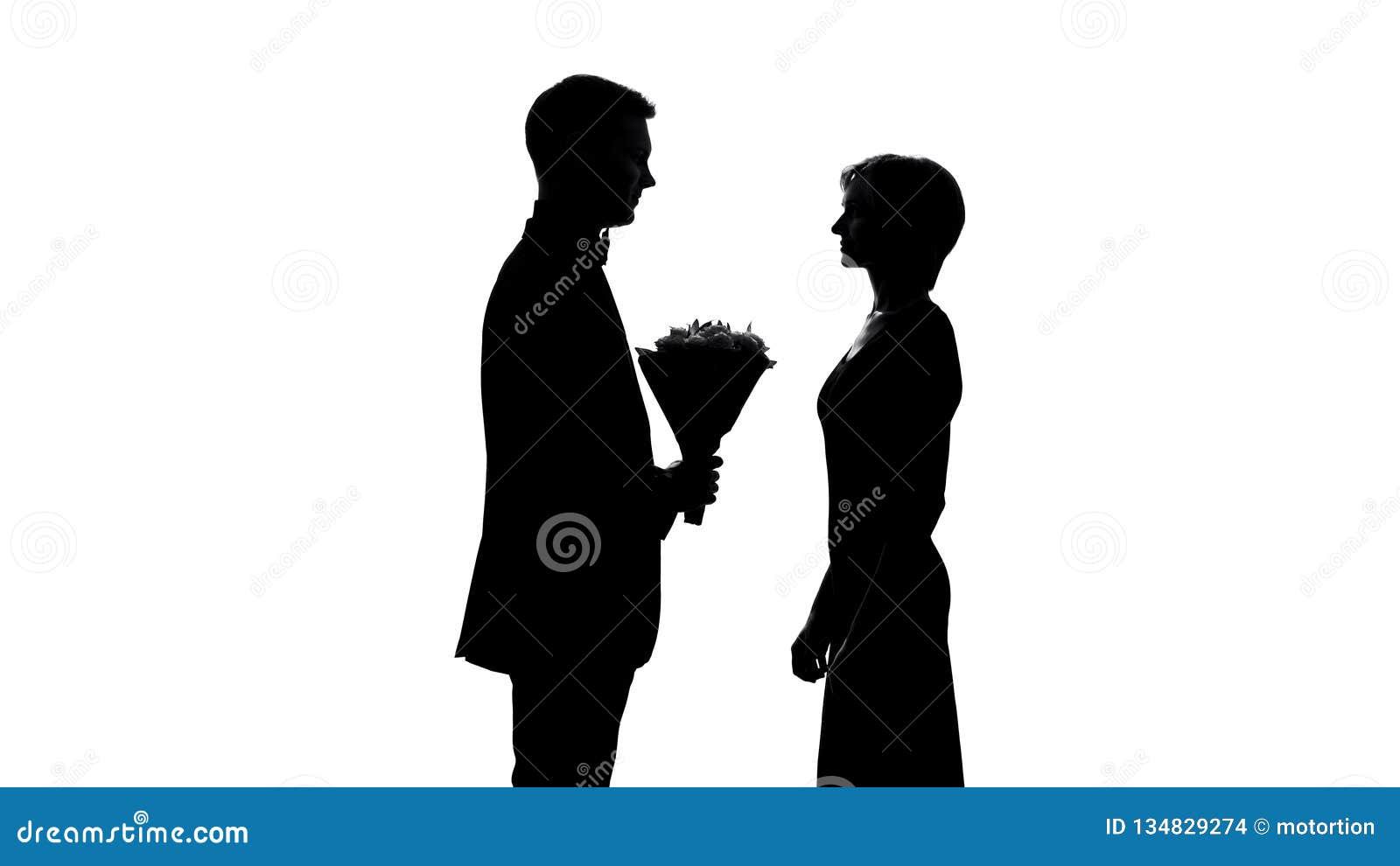 Homem novo que apresenta o ramalhete da flor da amiga, celebração do aniversário, primeira data