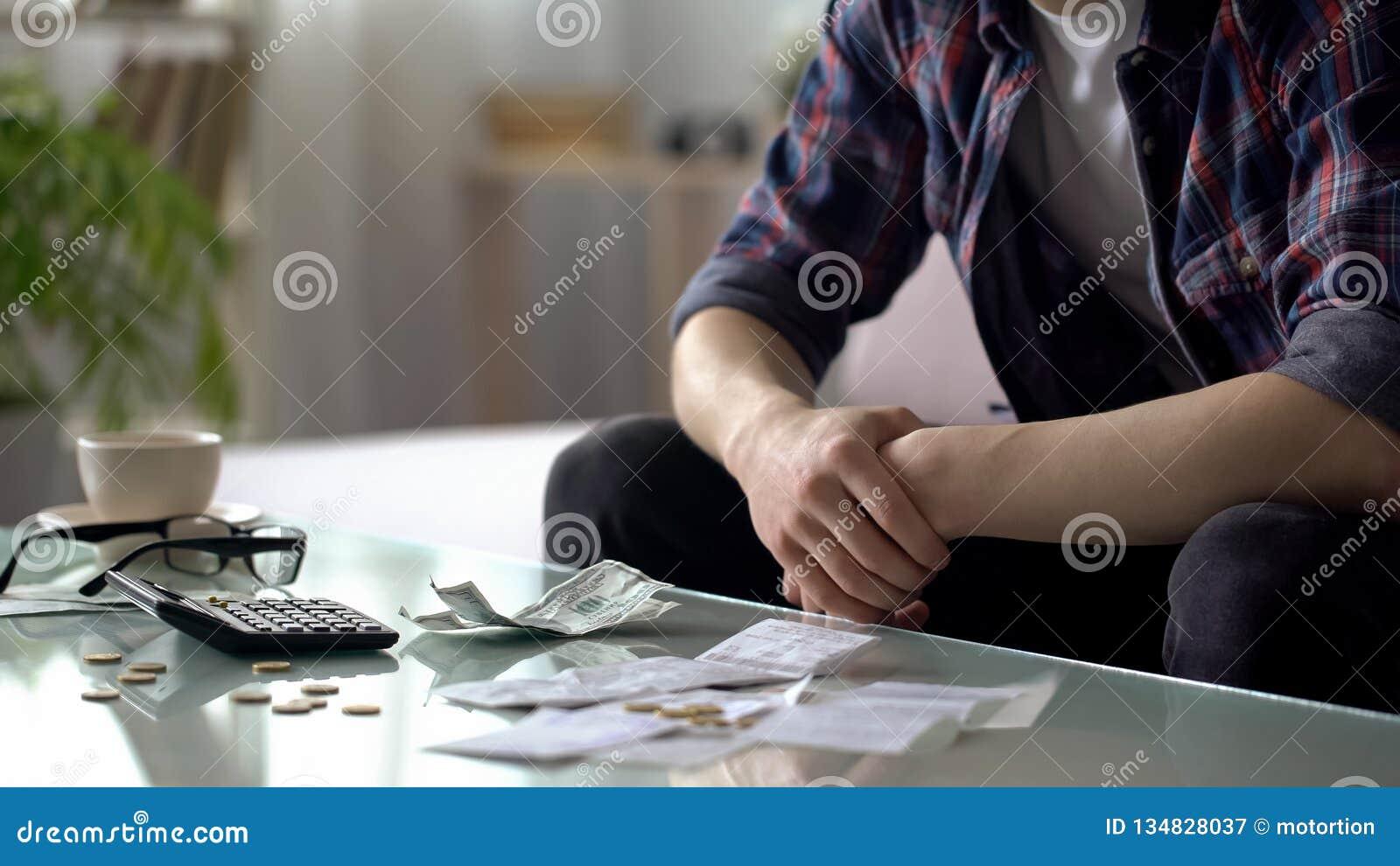 Homem novo que conta a finança da casa, os poucos dólares e os centavos deixados ao salário seguinte