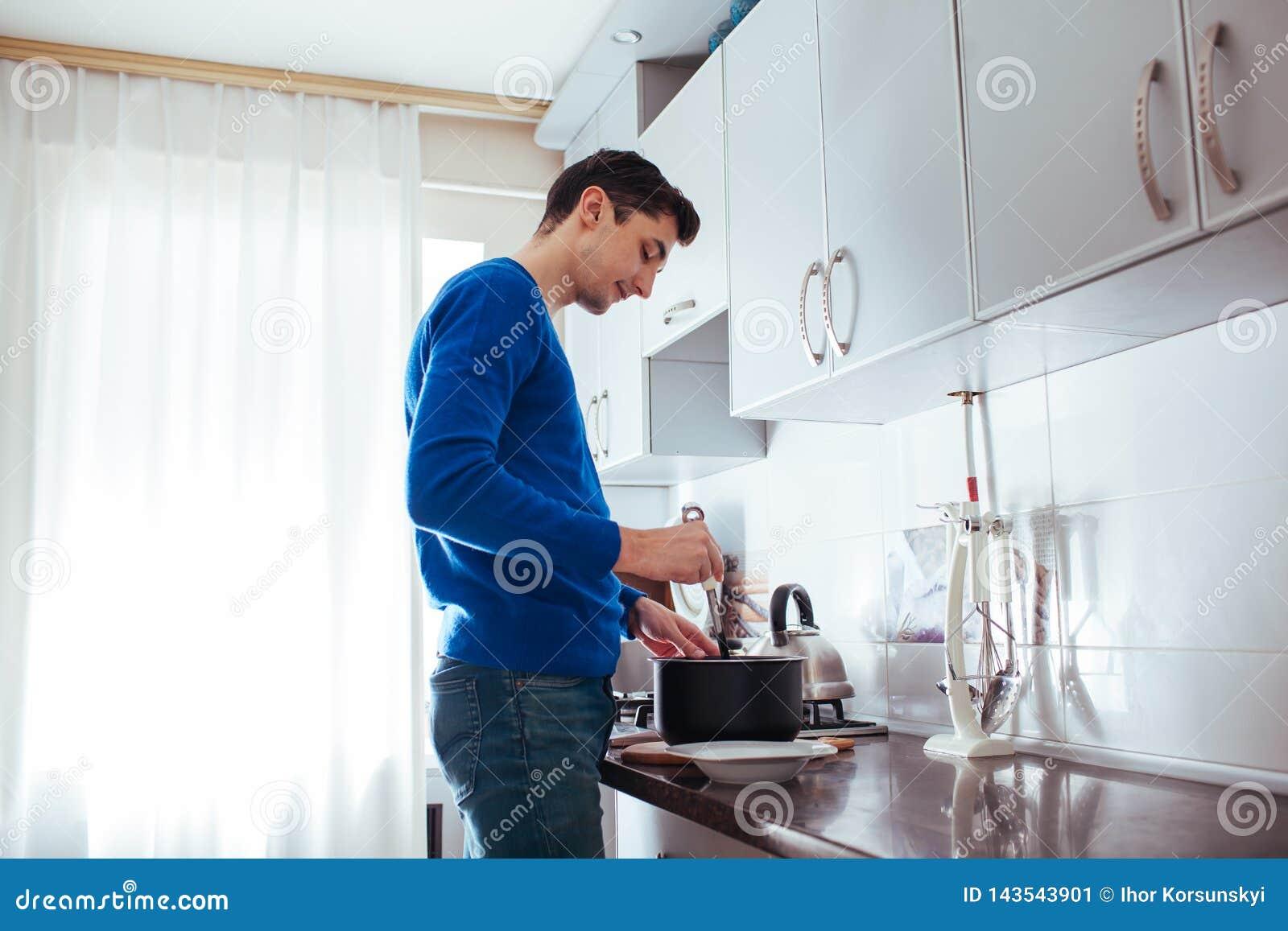 Homem novo que cozinha na cozinha em casa