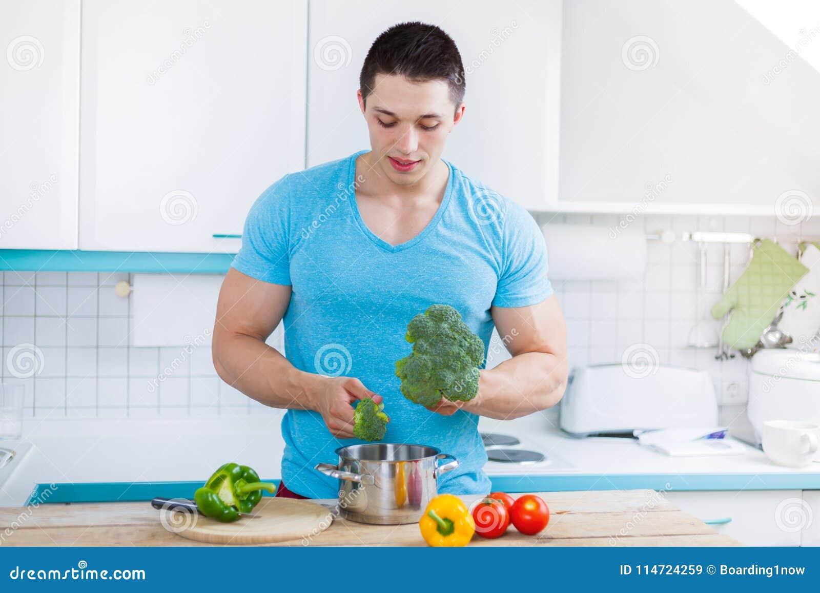 Homem novo que cozinha vegetais de preparação saudáveis da refeição no kitch
