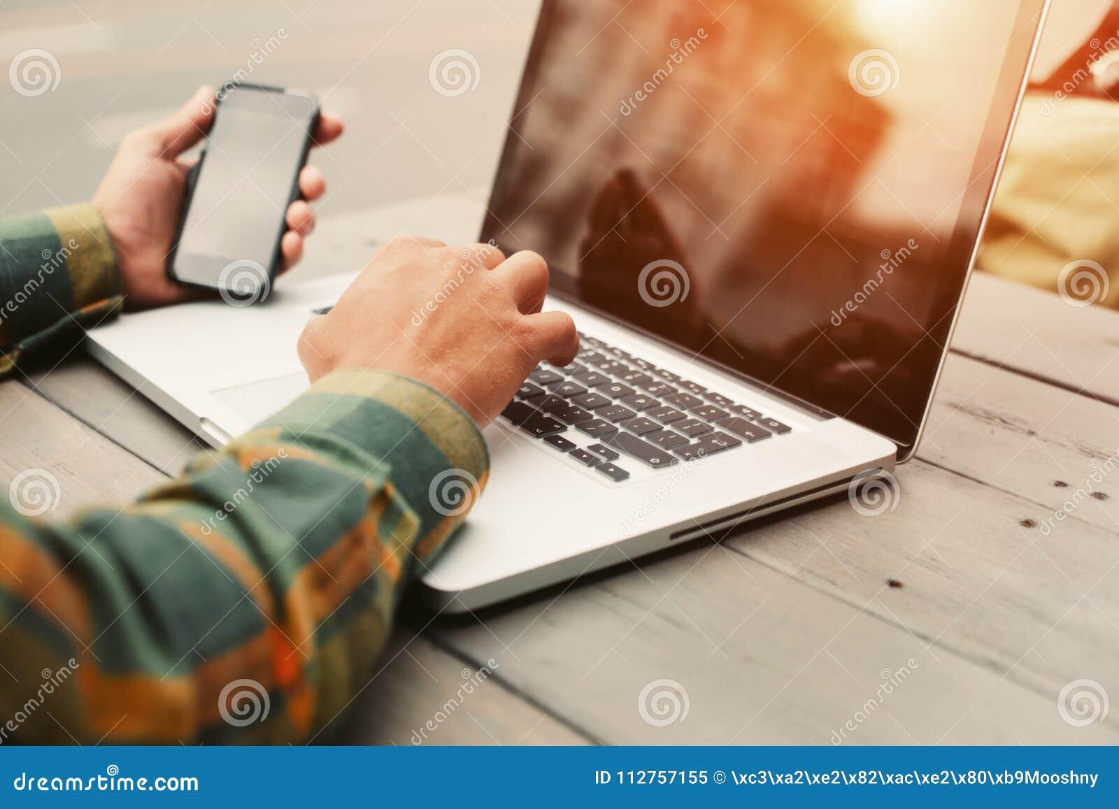Homem novo que datilografa no computador e que senta-se no café da rua, freelancer que faz seu trabalho fora