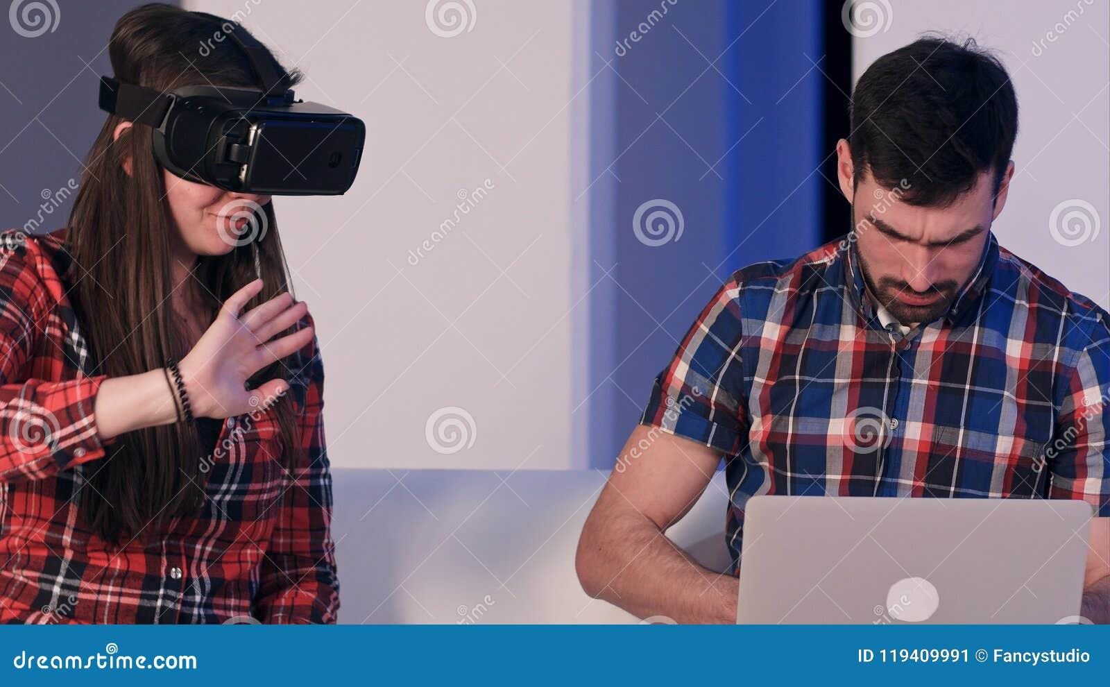 Homem novo que datilografa no portátil que fala à menina que veste vidros da realidade virtual