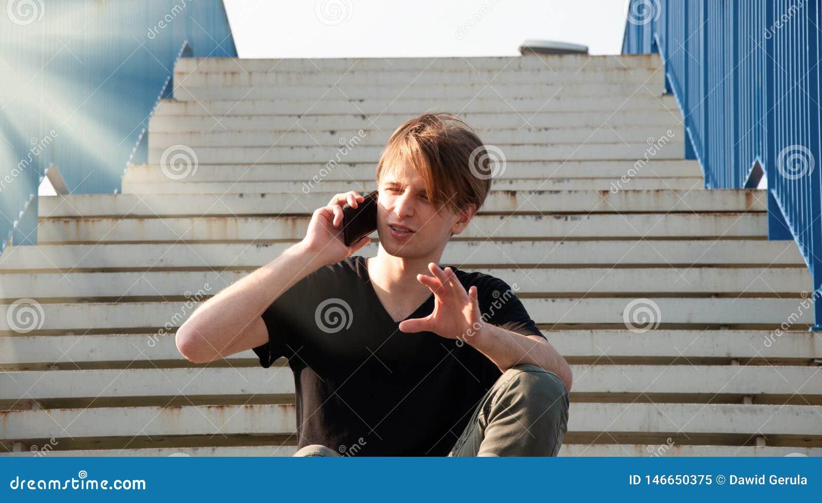 Homem novo que explica algo complicado, ao falar através do telefone, sentando-se nas escadas com cerca azul