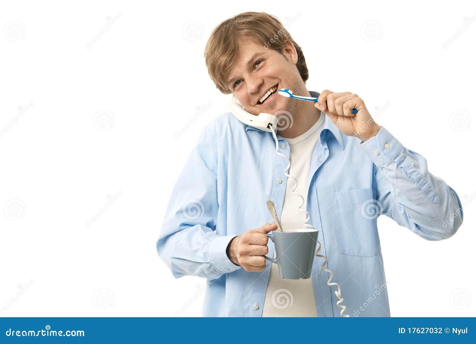 Homem novo que fala no telefone ao escovar os dentes