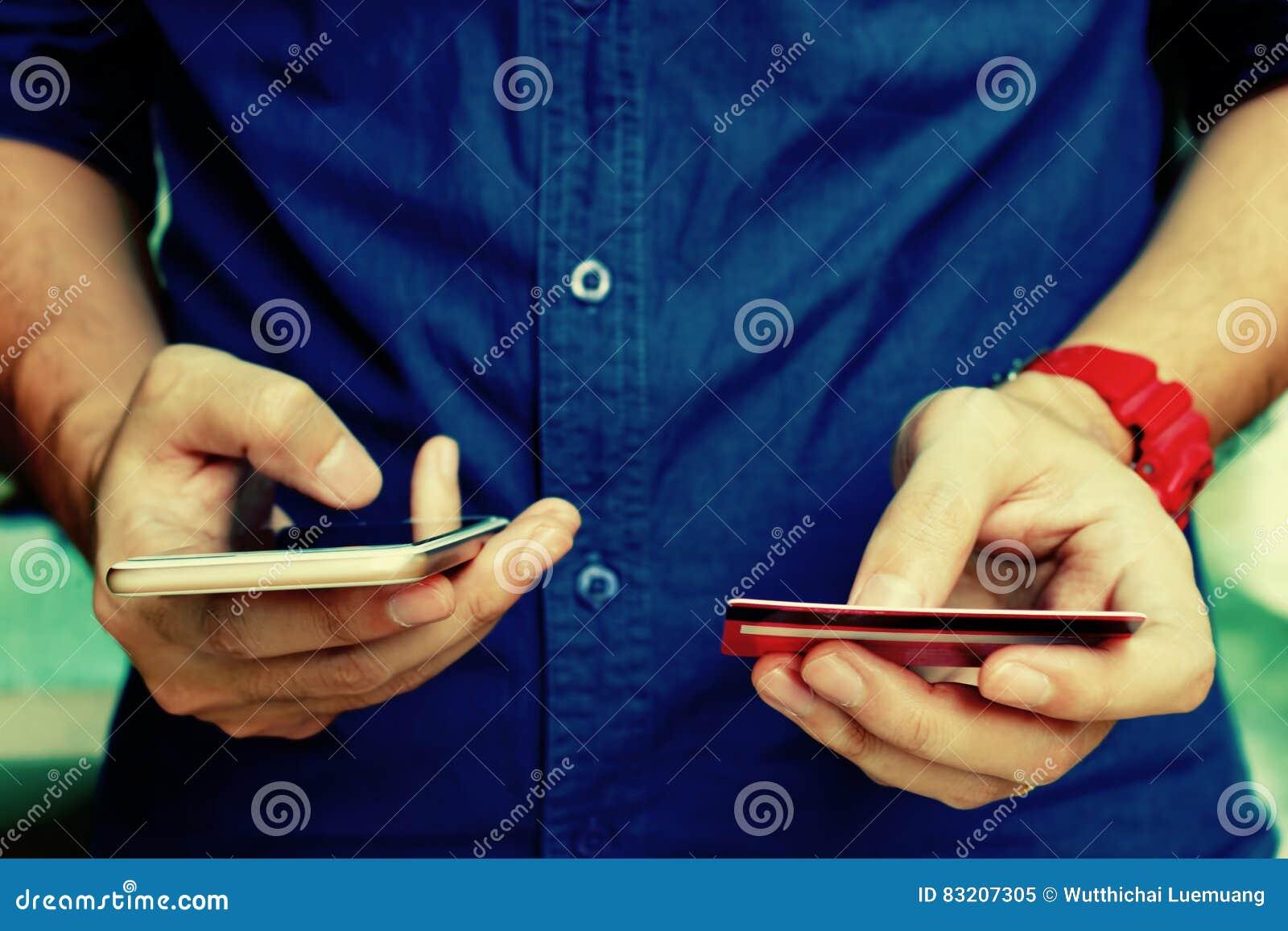 Homem novo que guarda o cartão de crédito e que usa o telefone esperto com compra