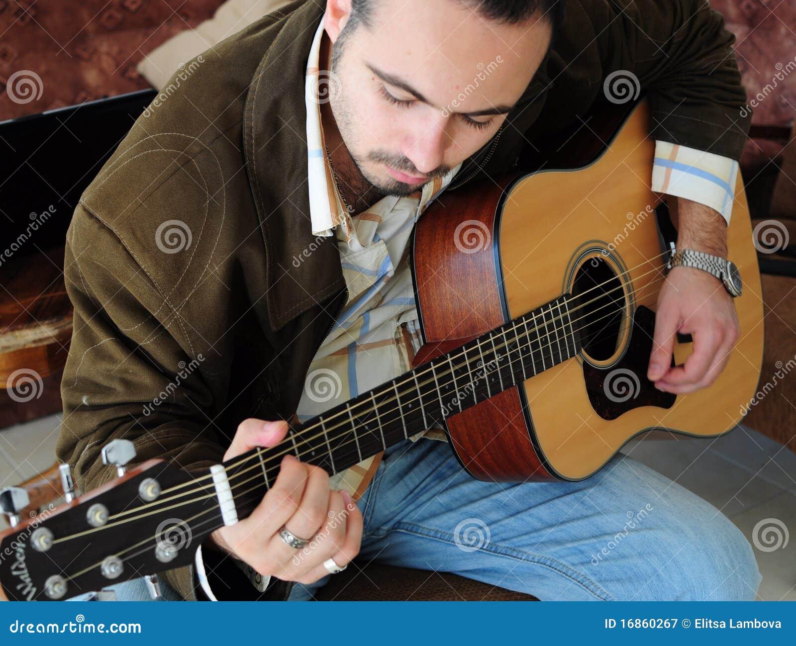 Homem novo que joga a guitarra