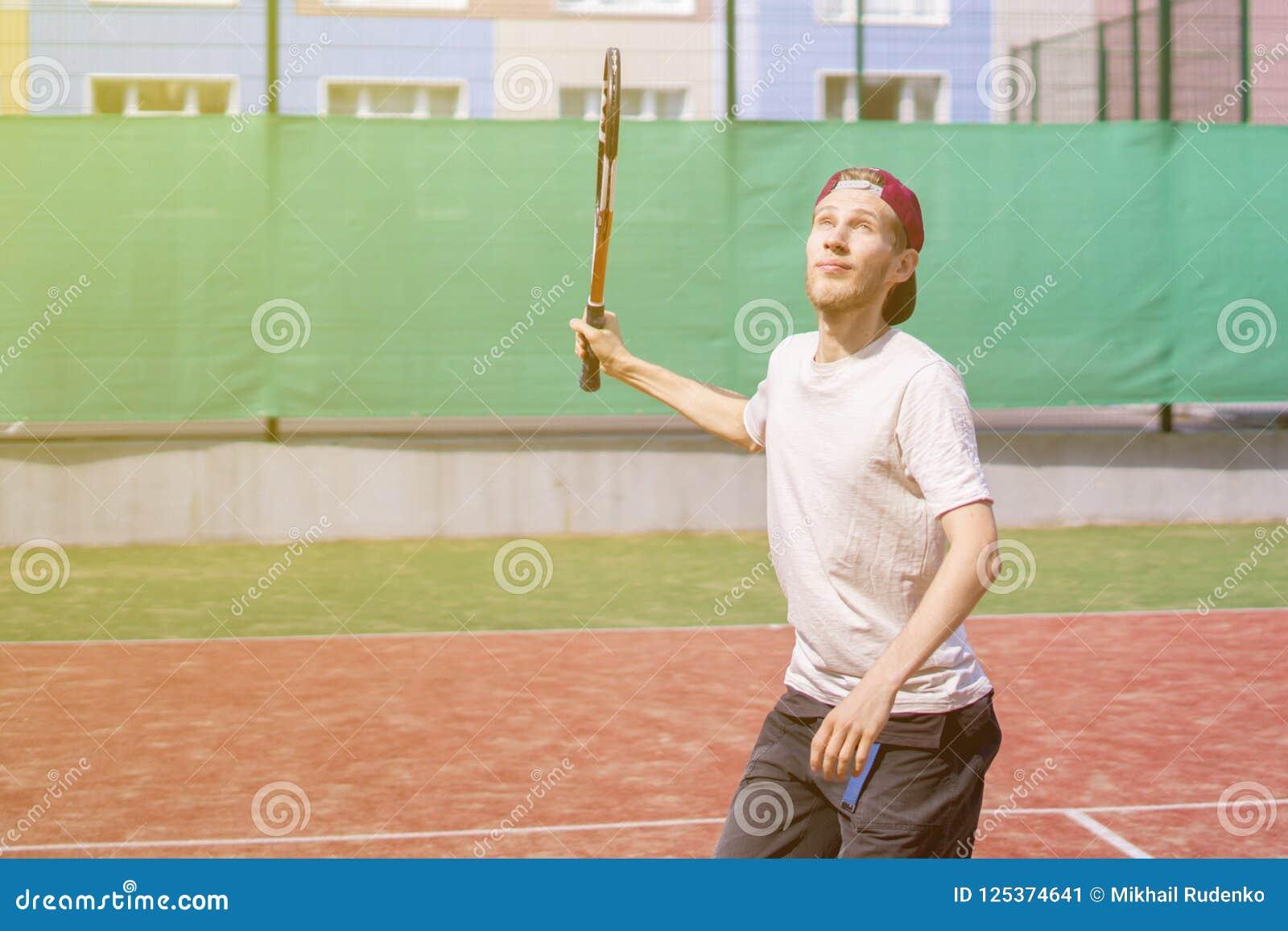 Homem novo que joga o tênis no tiro de fatura exterior da corte