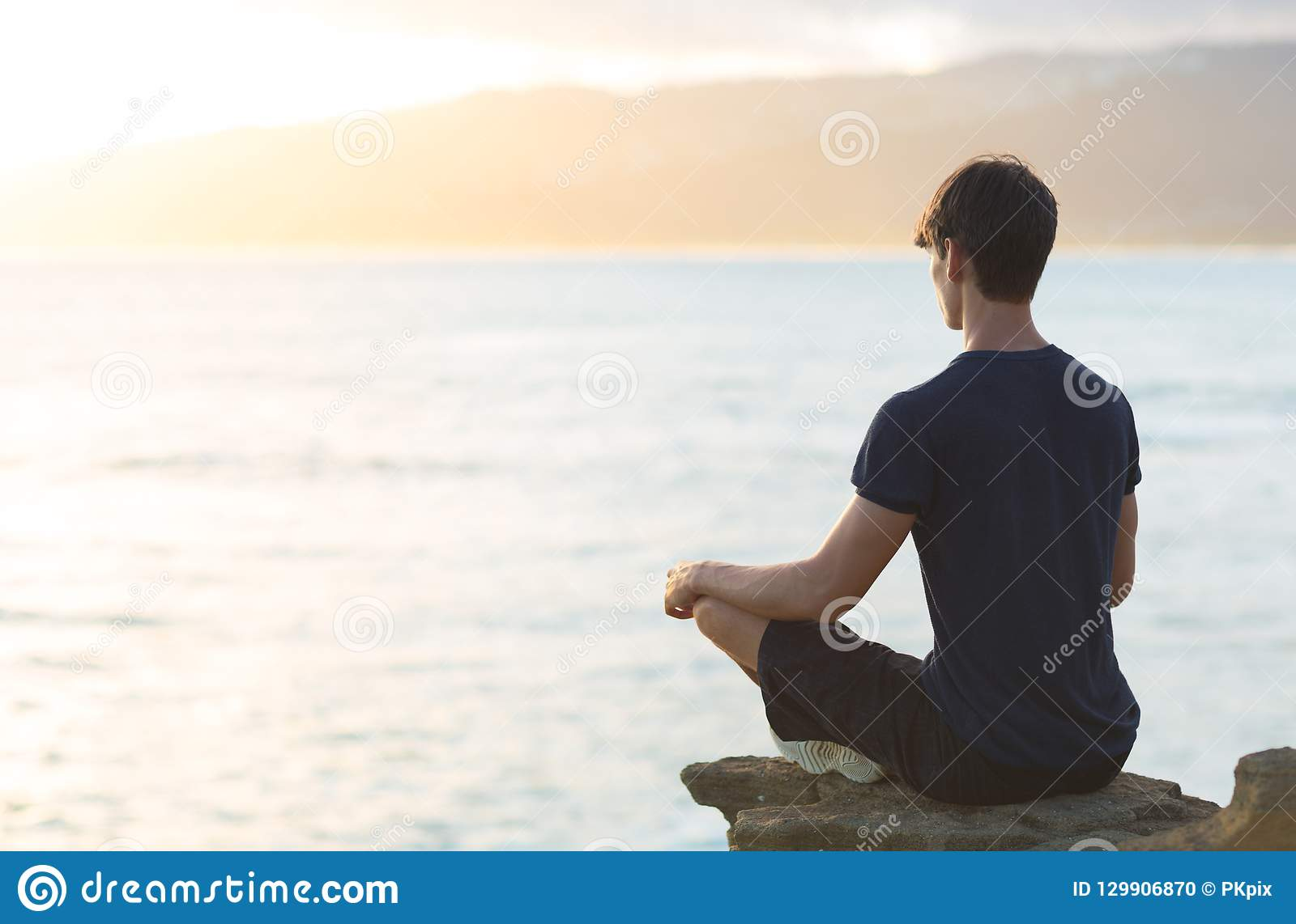 Homem novo que medita sobre o penhasco superior do oceano durante o por do sol