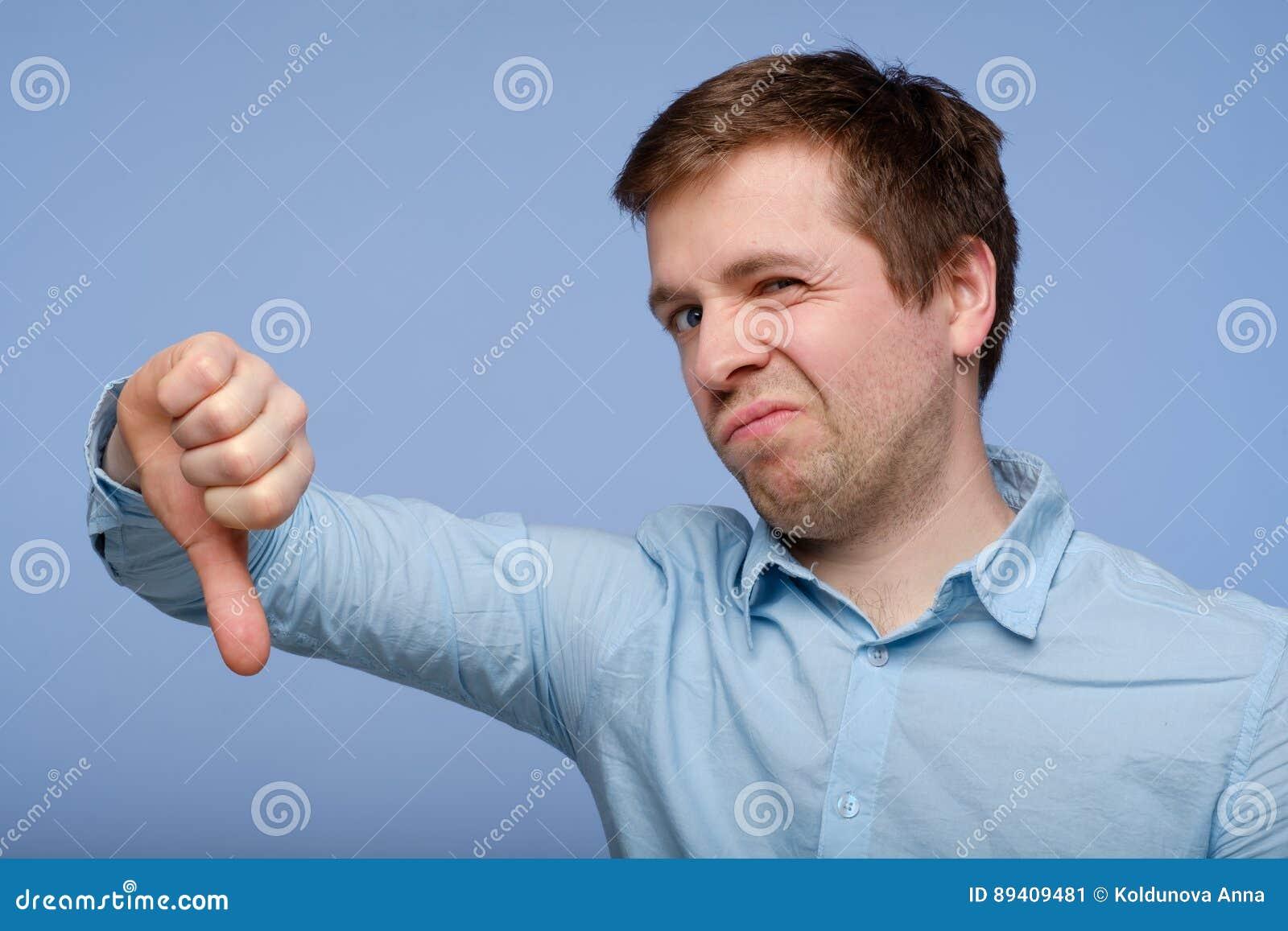 Homem novo que mostra o polegar para baixo