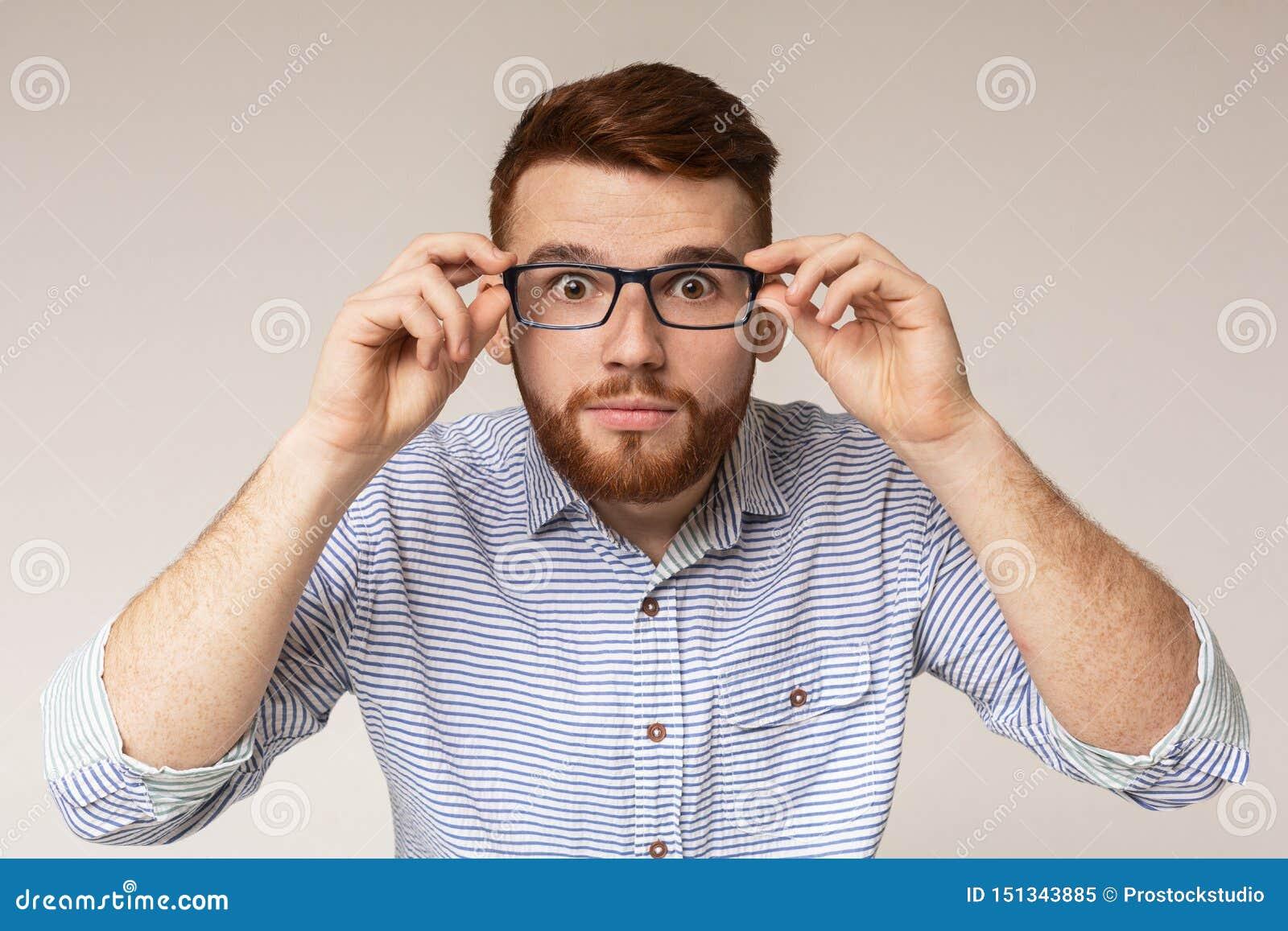 Homem novo que mostra seus olhos grandes nos vidros