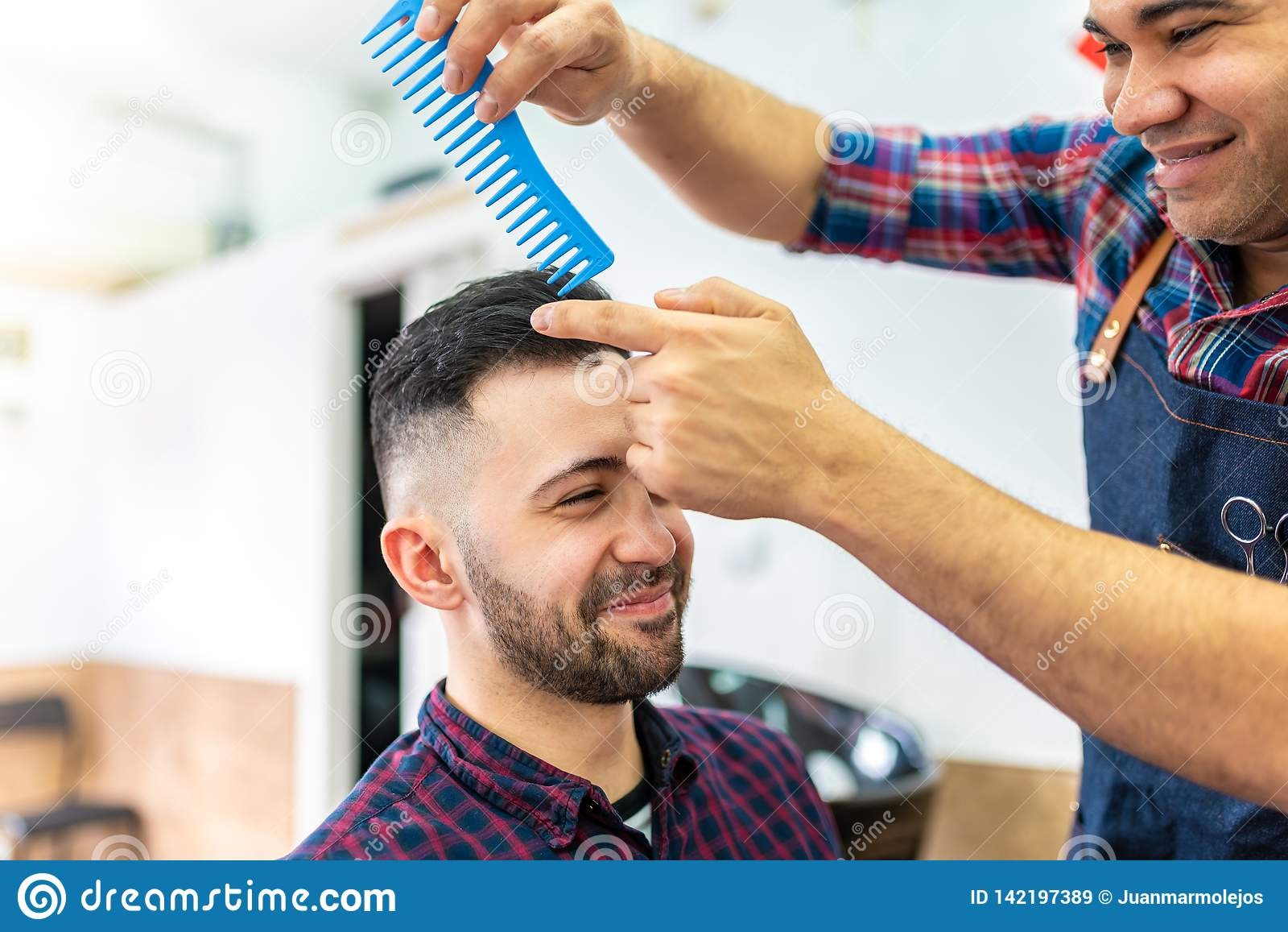 Homem novo que obtém um penteado em um barbeiro