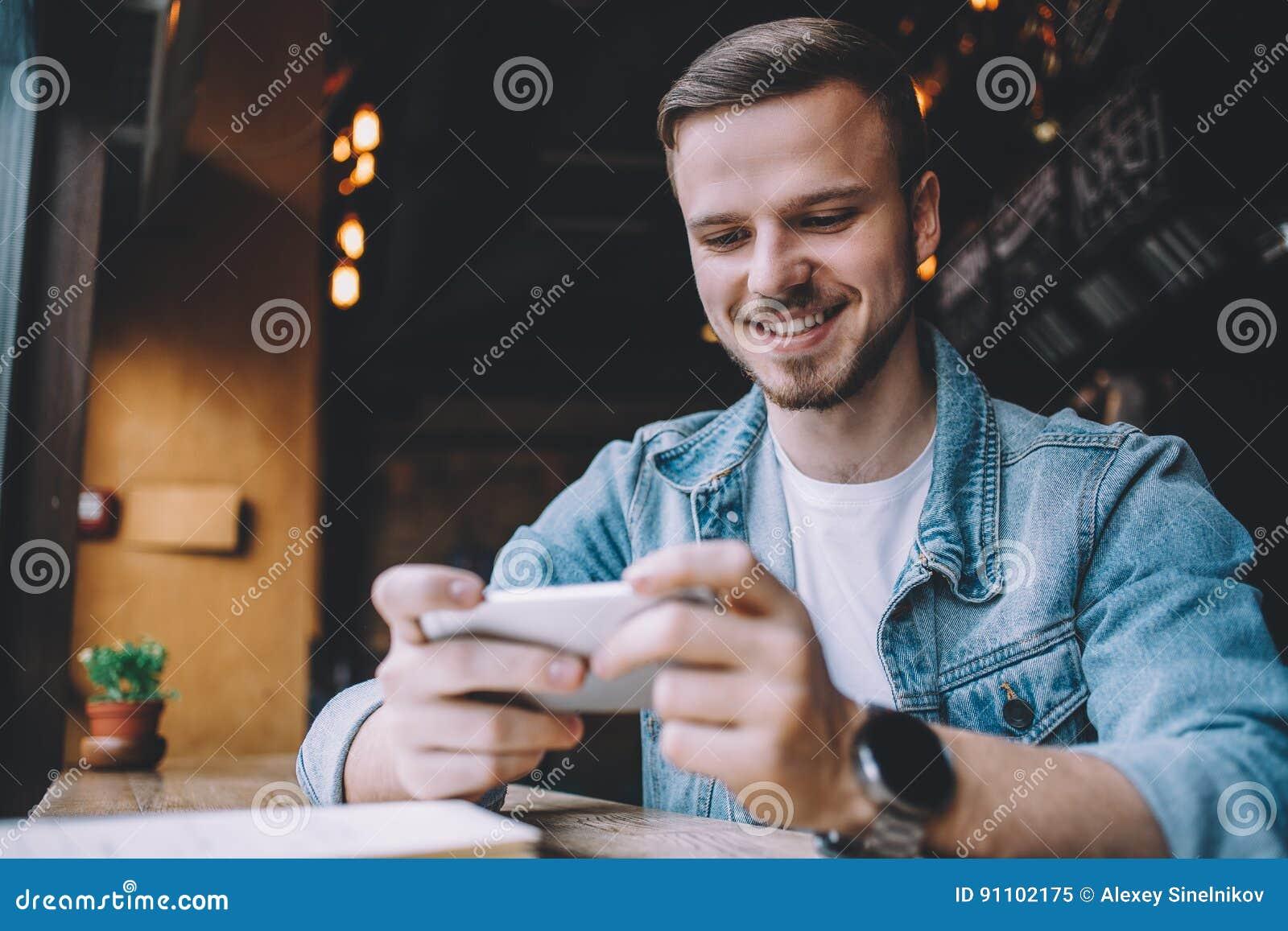 Homem novo que olha o telefone, sentando-se no restaurante