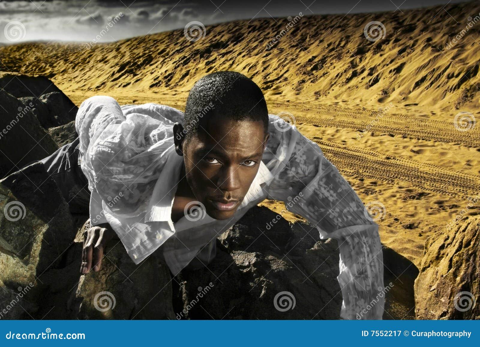 Homem novo que rasteja em rochas do deserto