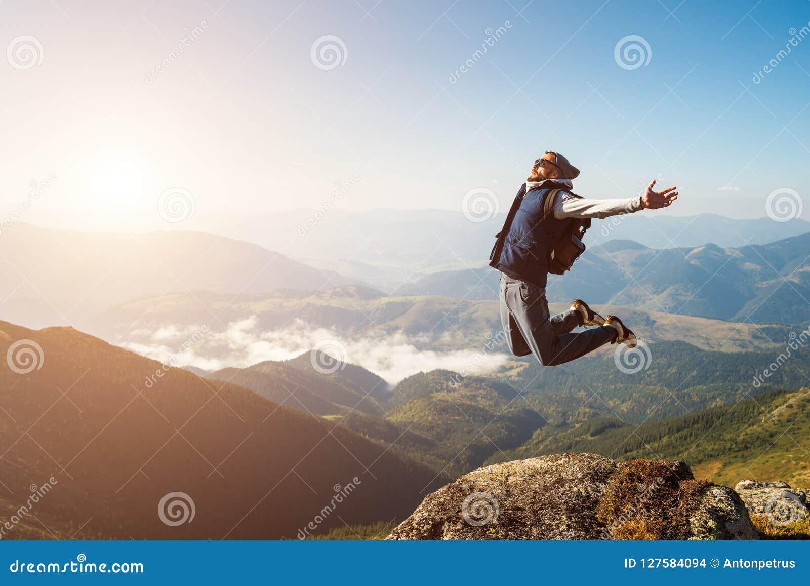 Homem novo que salta sobre uma montanha contra o céu