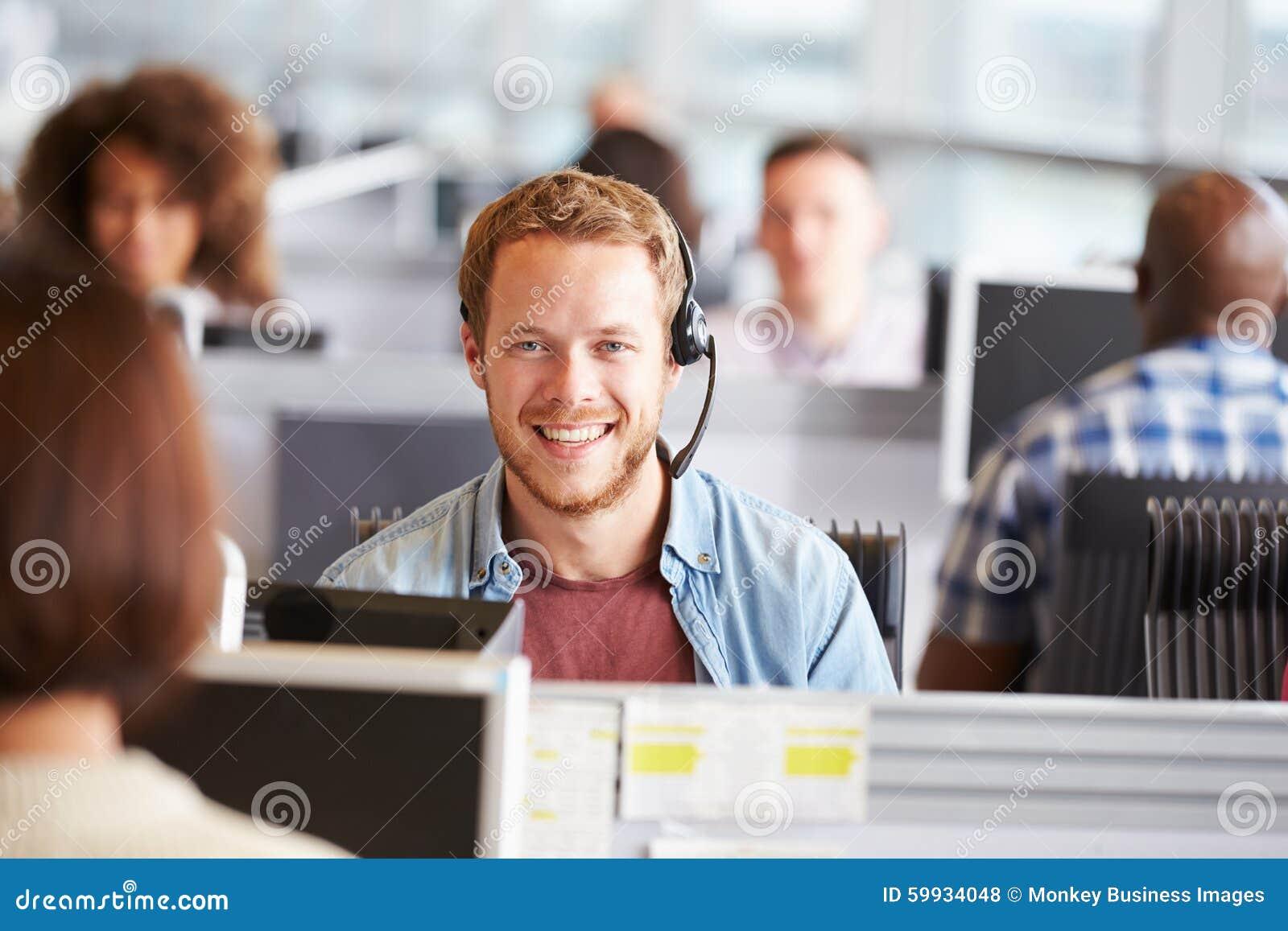 Homem novo que trabalha em um centro de chamada, olhando à câmera