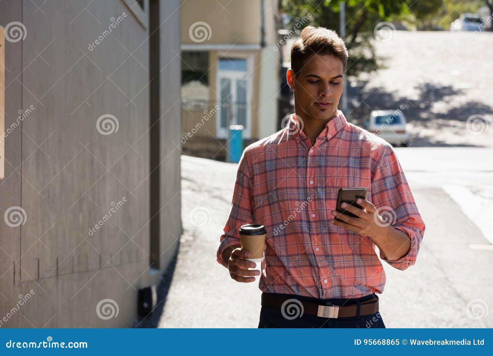 Homem novo que usa o telefone ao andar construindo