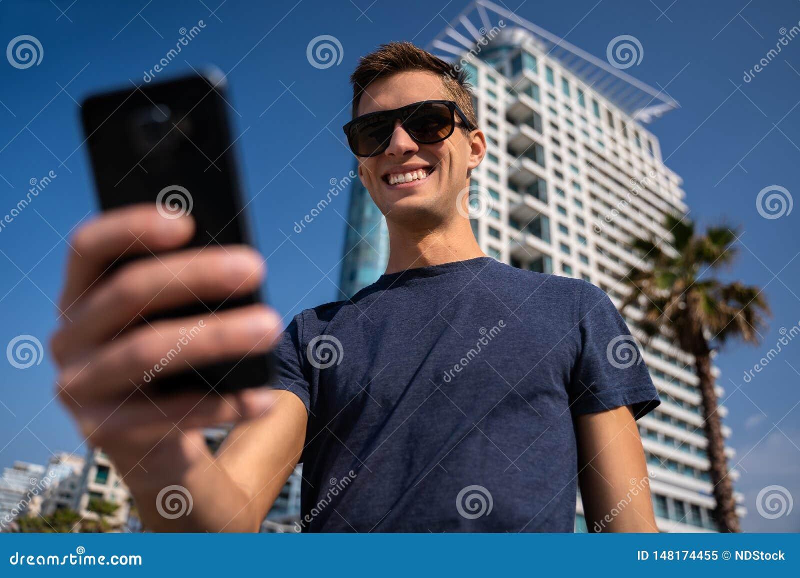 Homem novo que usa o telefone Skyline da cidade no fundo