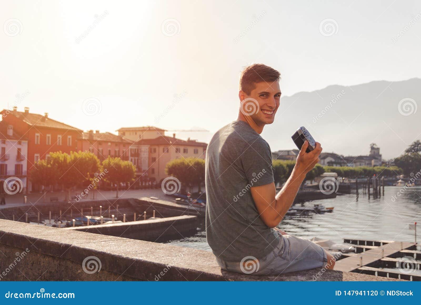 Homem novo que usa uma c?mera do vintage na frente do passeio do lago em Ascona