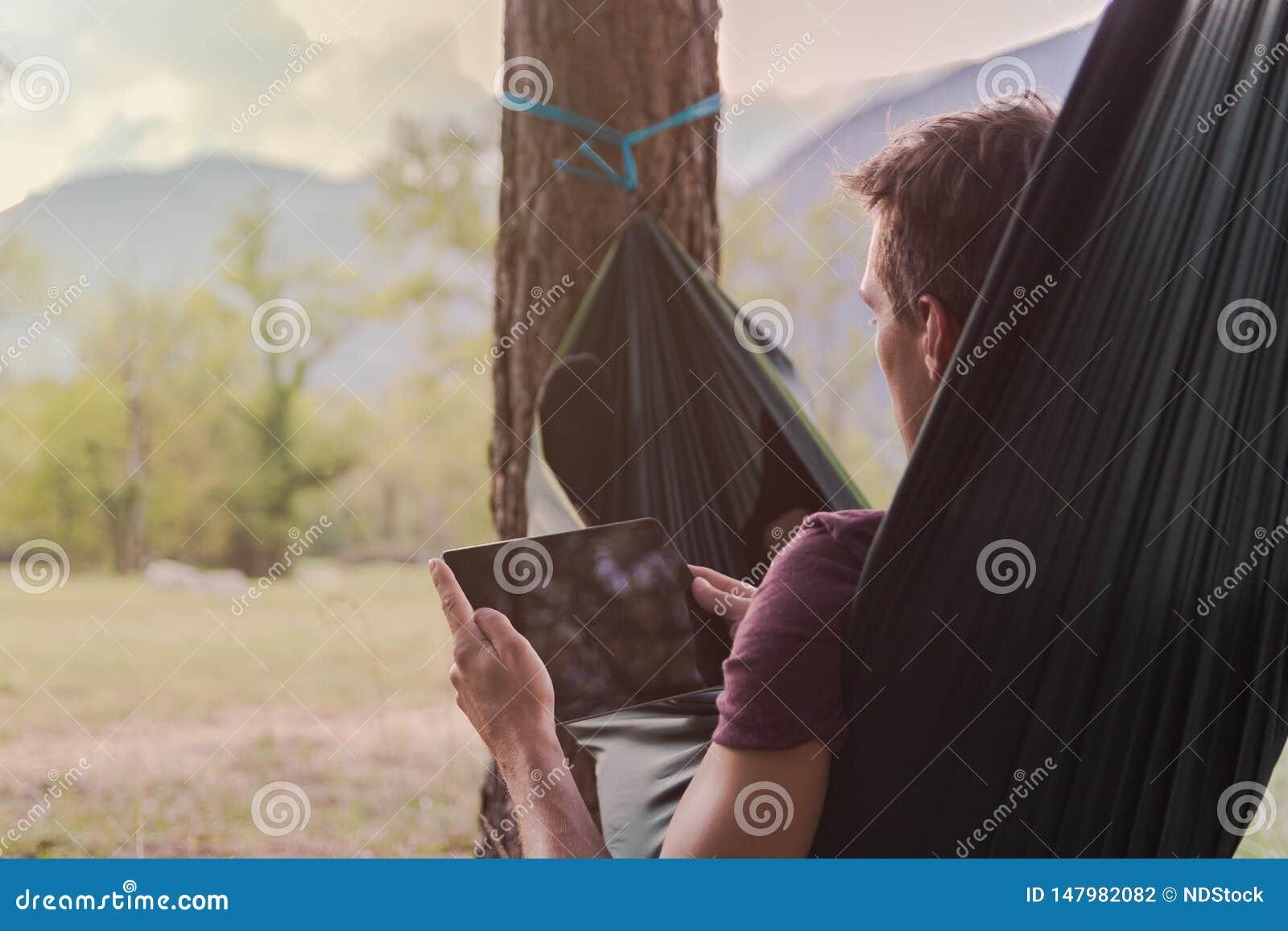 Homem novo que usa uma tabuleta em uma rede