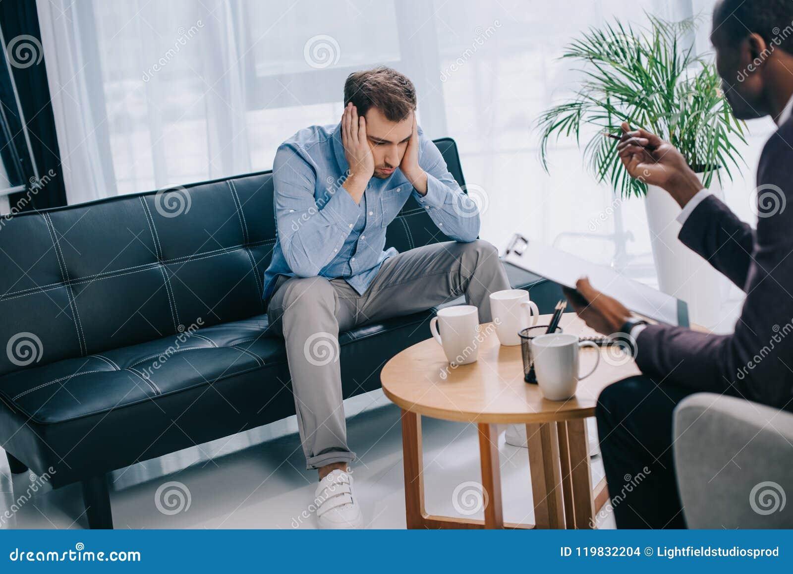 Homem novo virado que senta-se no sofá e no psiquiatra