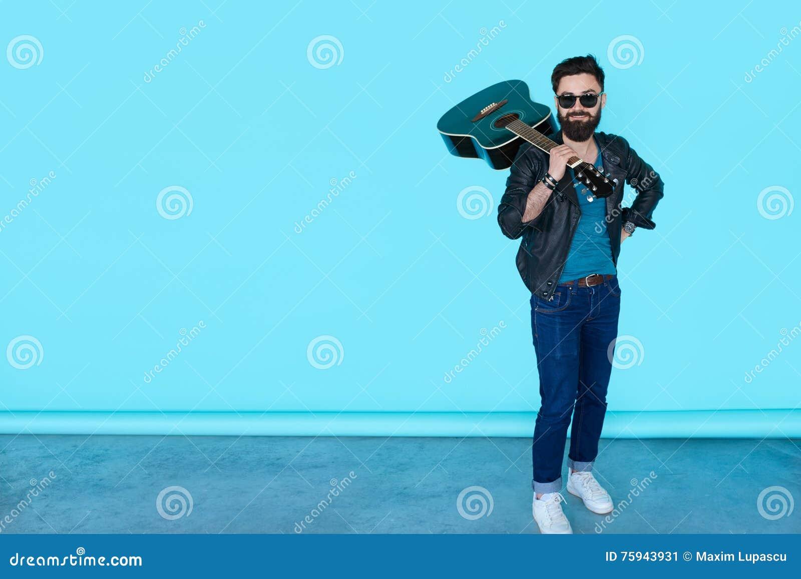 Homem ocasional considerável no casaco de cabedal preto com guitarra