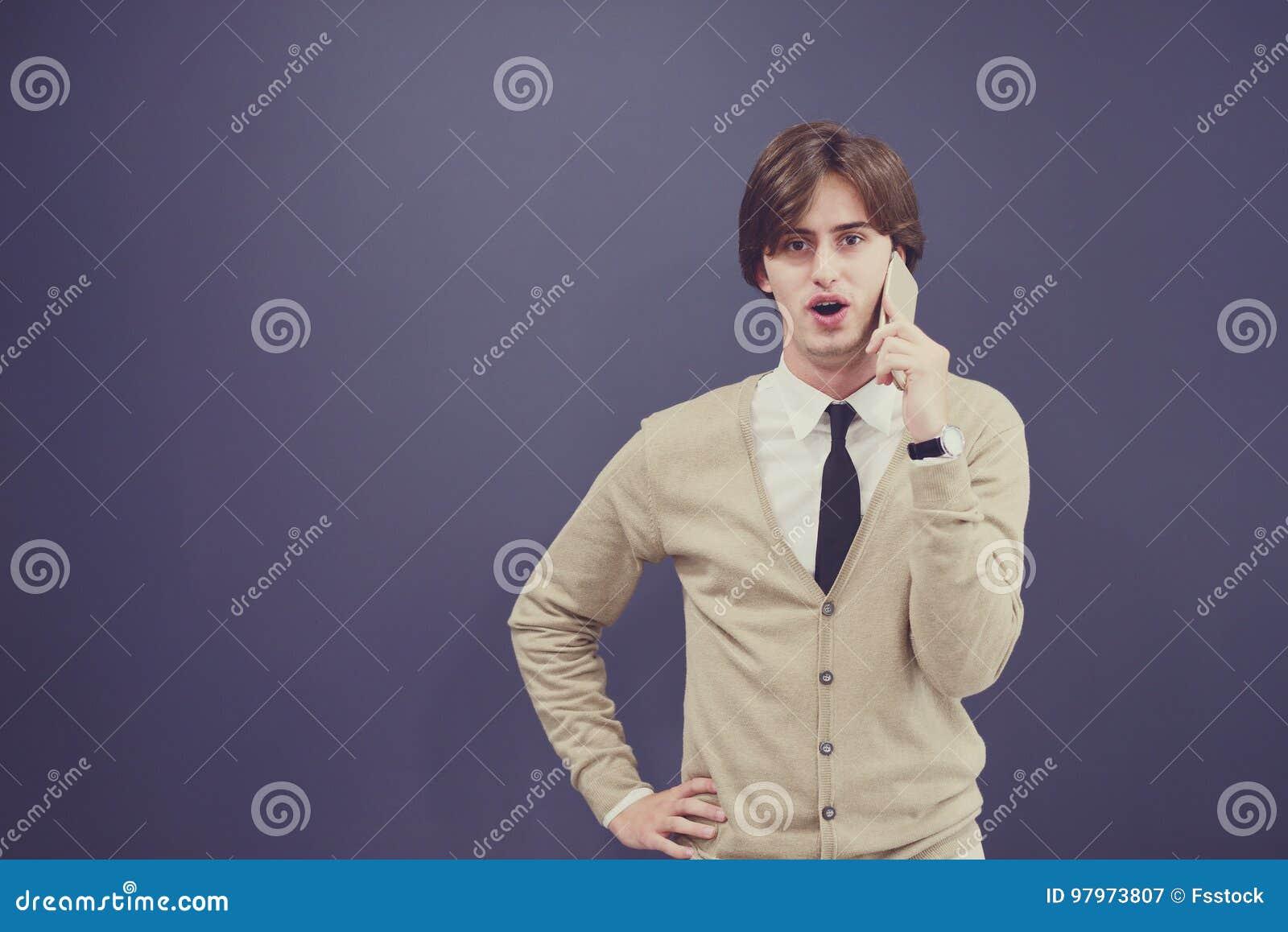 Homem ocasional novo que fala no telefone isolado no fundo branco