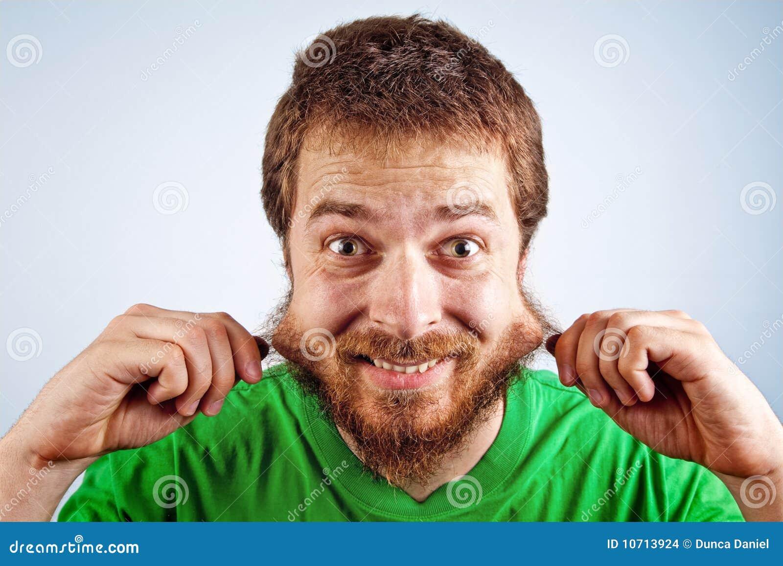 Homem parvo engraçado que agarra sua barba peludo