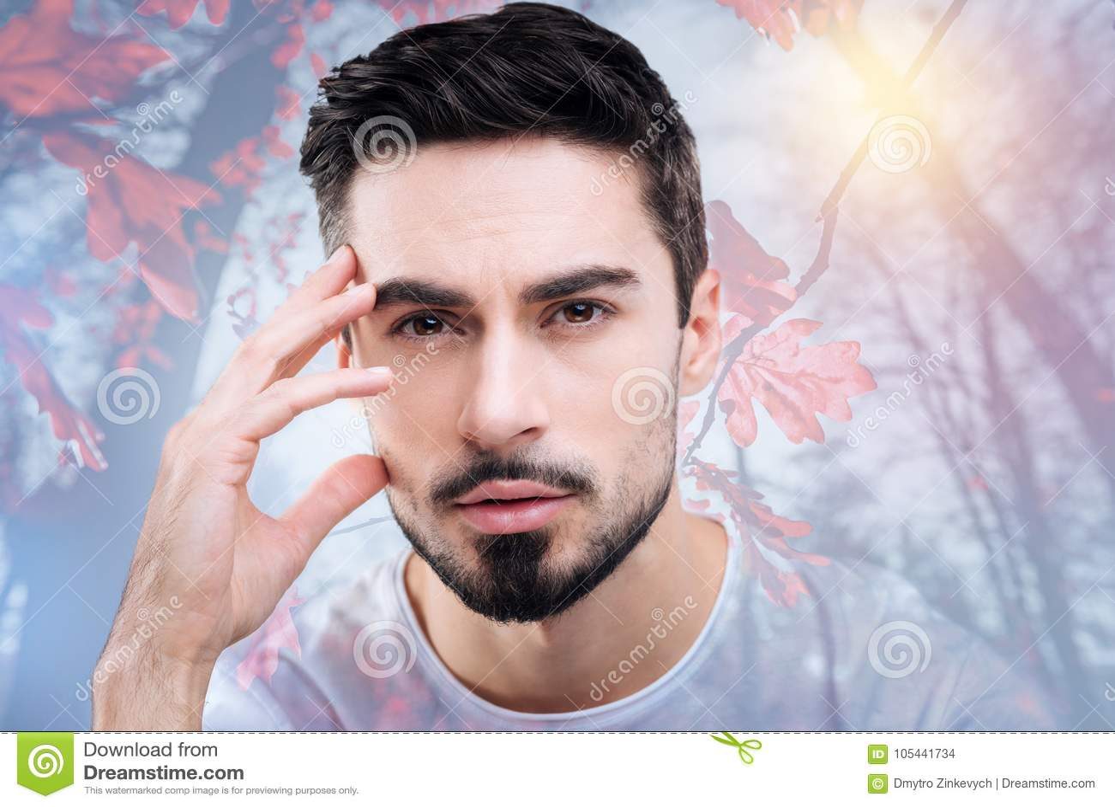 Homem pensativo novo que olha interessado ao admirar a beleza da natureza