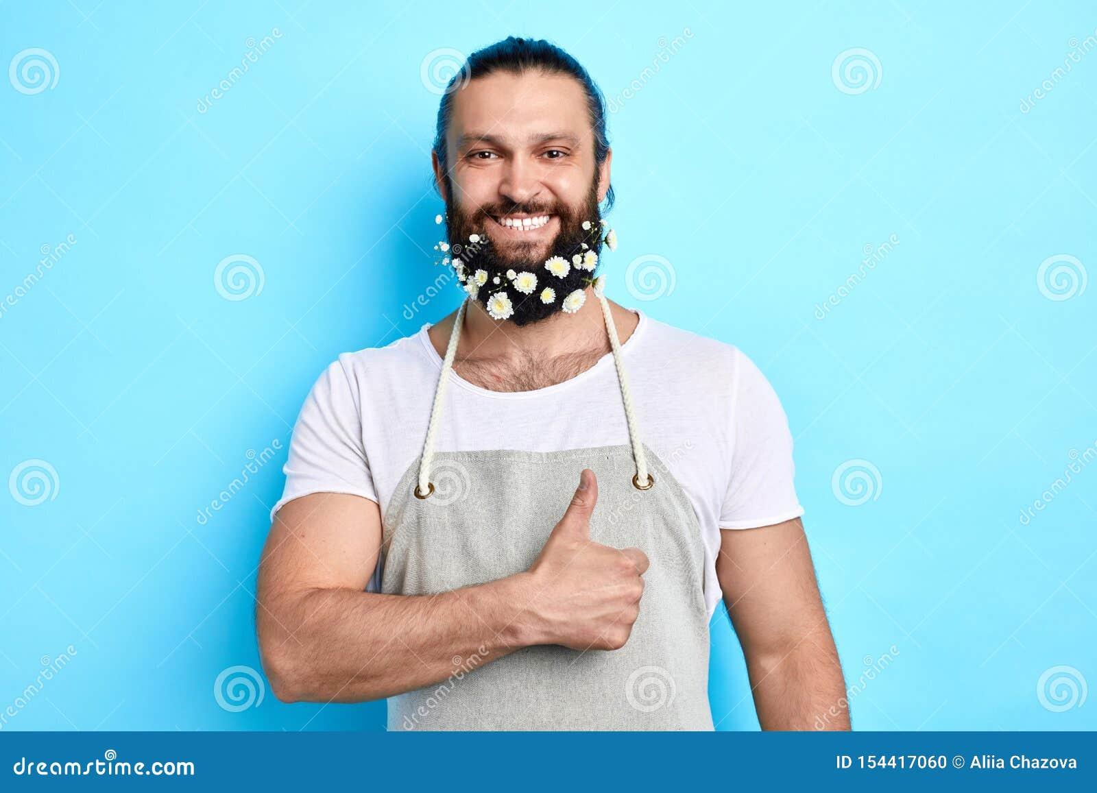 Homem positivo alegre com a barba decorada com as flores que ahowing o polegar acima
