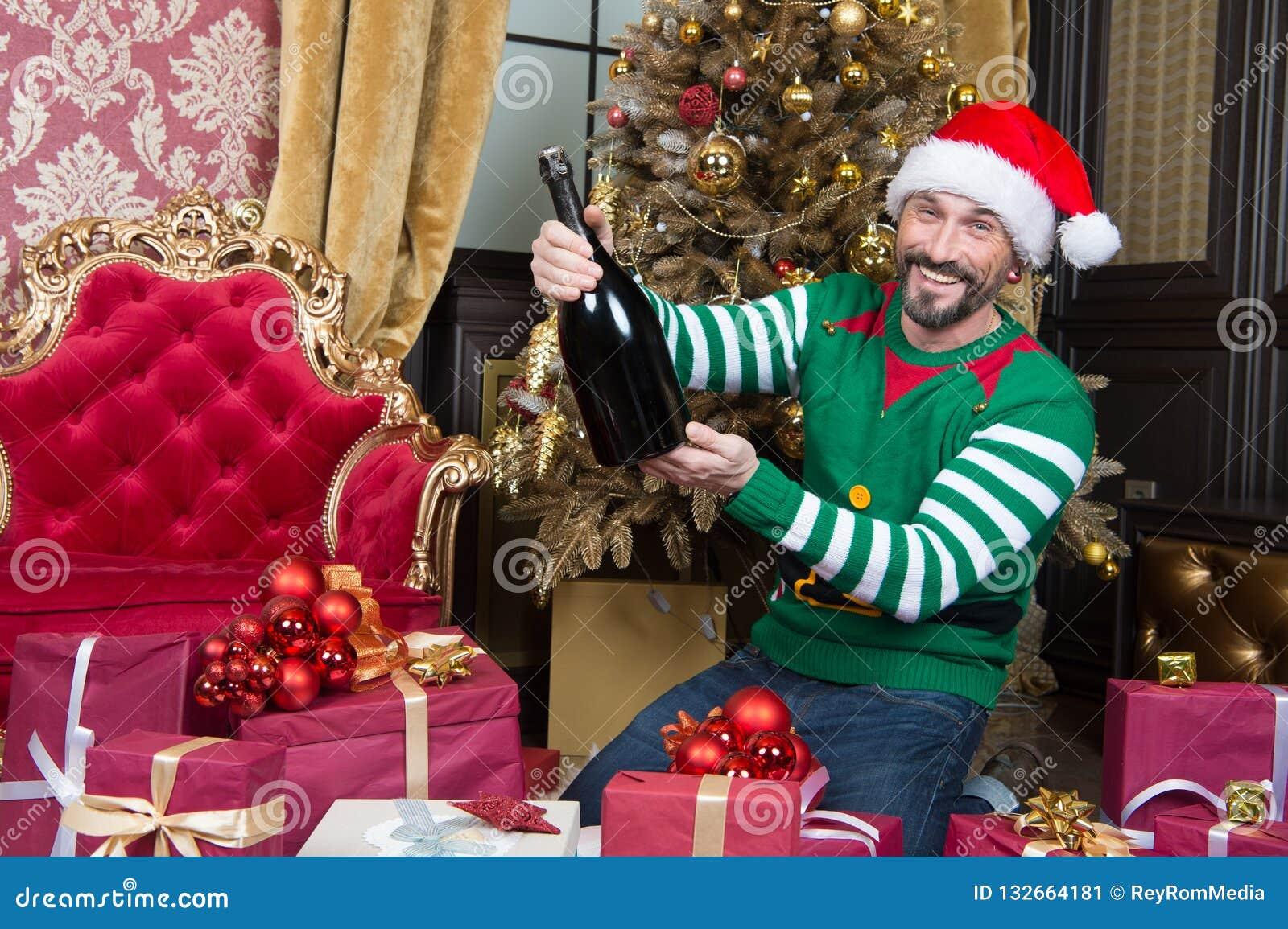Homem positivo que ri ao sentar-se com a garrafa grande perto da árvore de Natal
